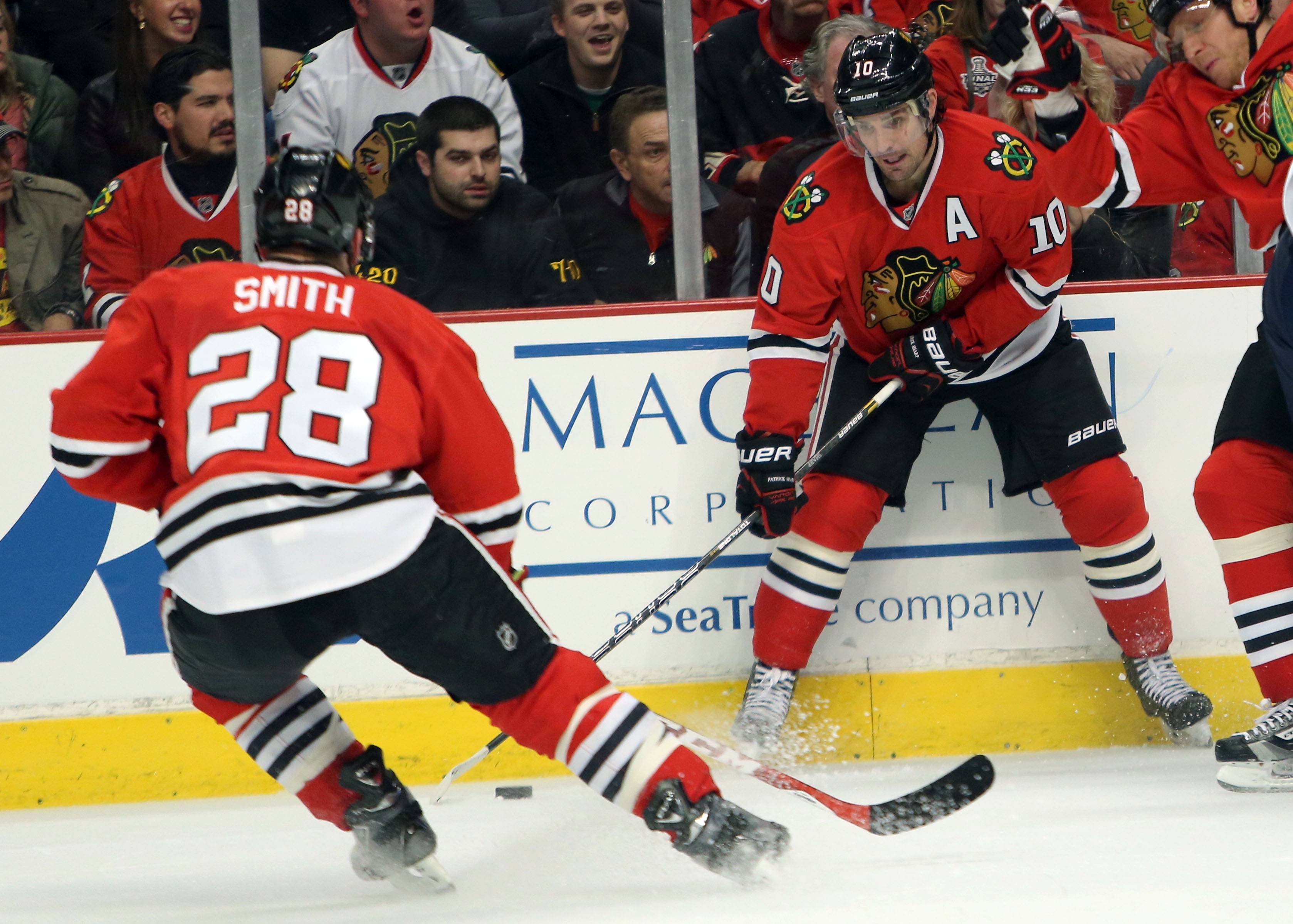 Chicago Blackhawks left wing Patrick Sharp, right, passes to Chicago Blackhawks right wing Ben Smith.