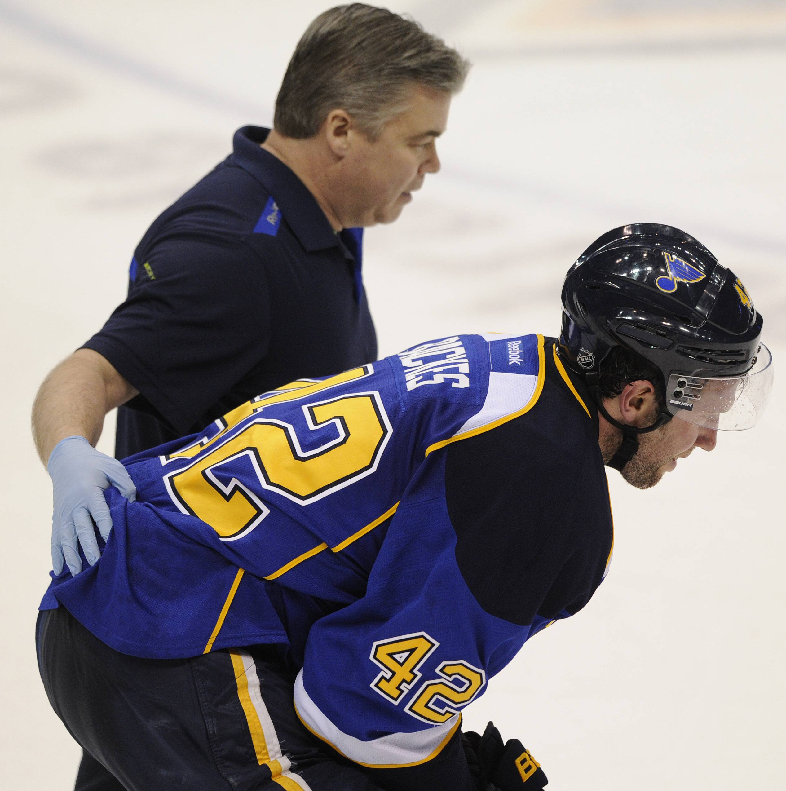 The St. Louis Blues' David Backes (42) is helped off the ice by a Blues trainer against the Chicago Blackhawks during the third period in Game 2 of a first-round NHL hockey playoff series, Saturday, April 19, 2014, in St. Louis.
