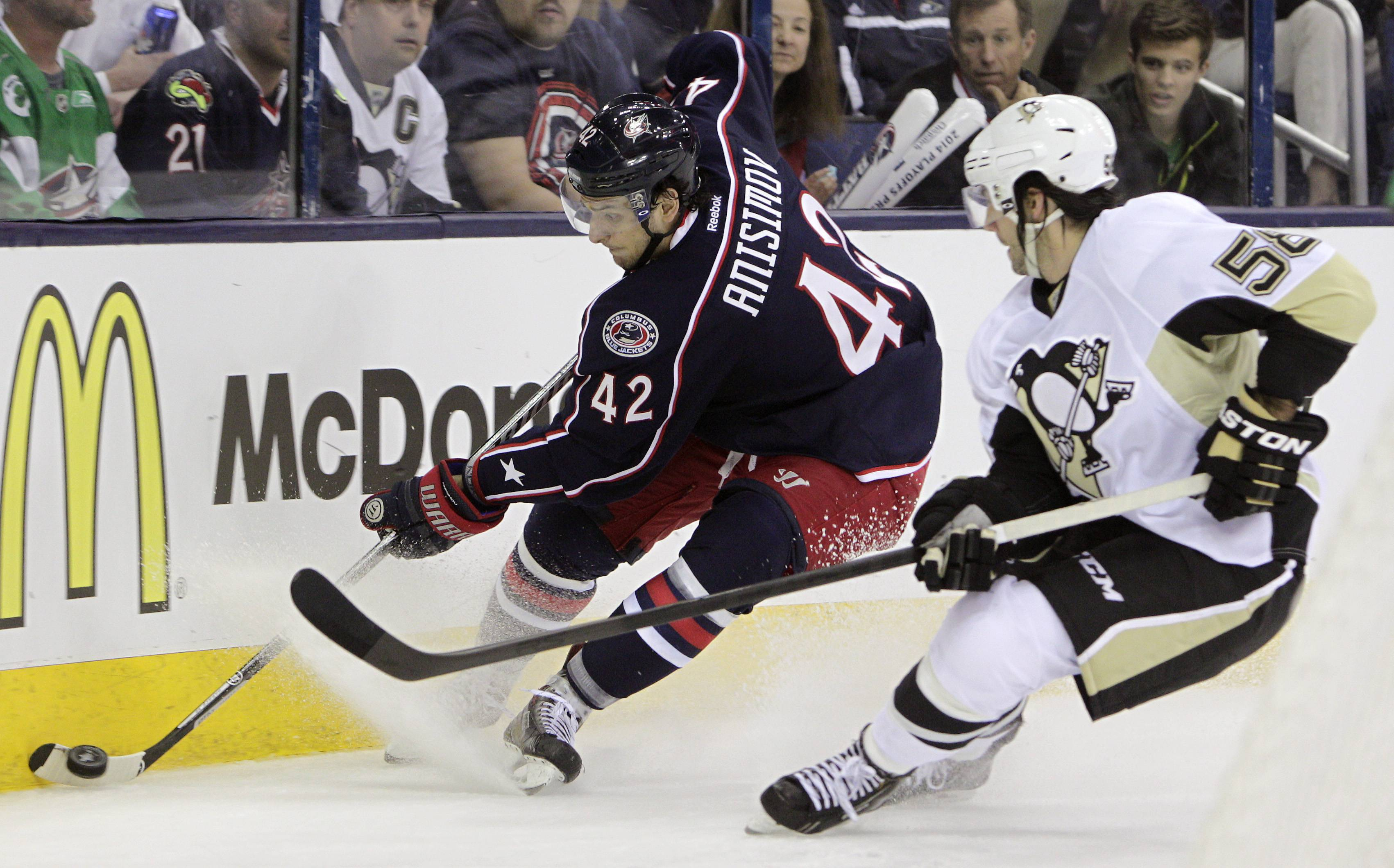 Columbus Blue Jackets' Artem Anisimov, left, of Russia, tries to clear the puck as Pittsburgh Penguins' Kris Letang defends during the second period of a first-round NHL playoff hockey game Monday, April 21, 2014, in Columbus, Ohio.