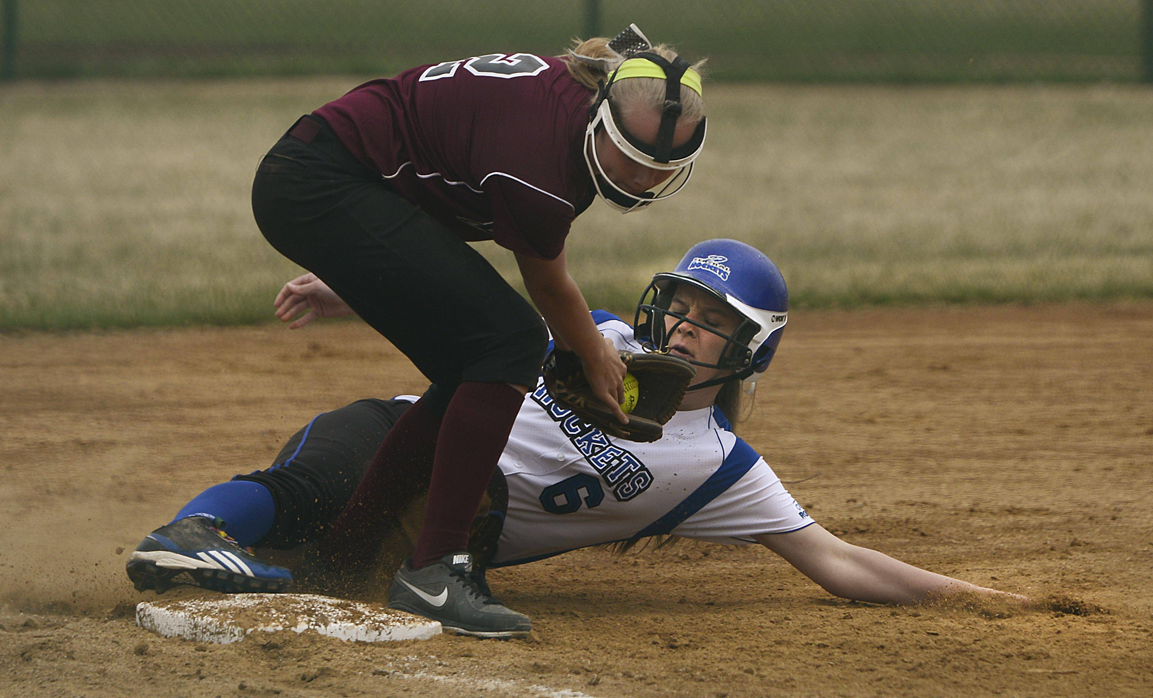 Burlington Central's Lindsey Strohmaier bends her leg around Marengo's Leah Secor to reach third base safely Monday on a hit by teammate Tori Harvey in the sixth inning in Marengo. Both players were stranded on base after reaching with no outs.