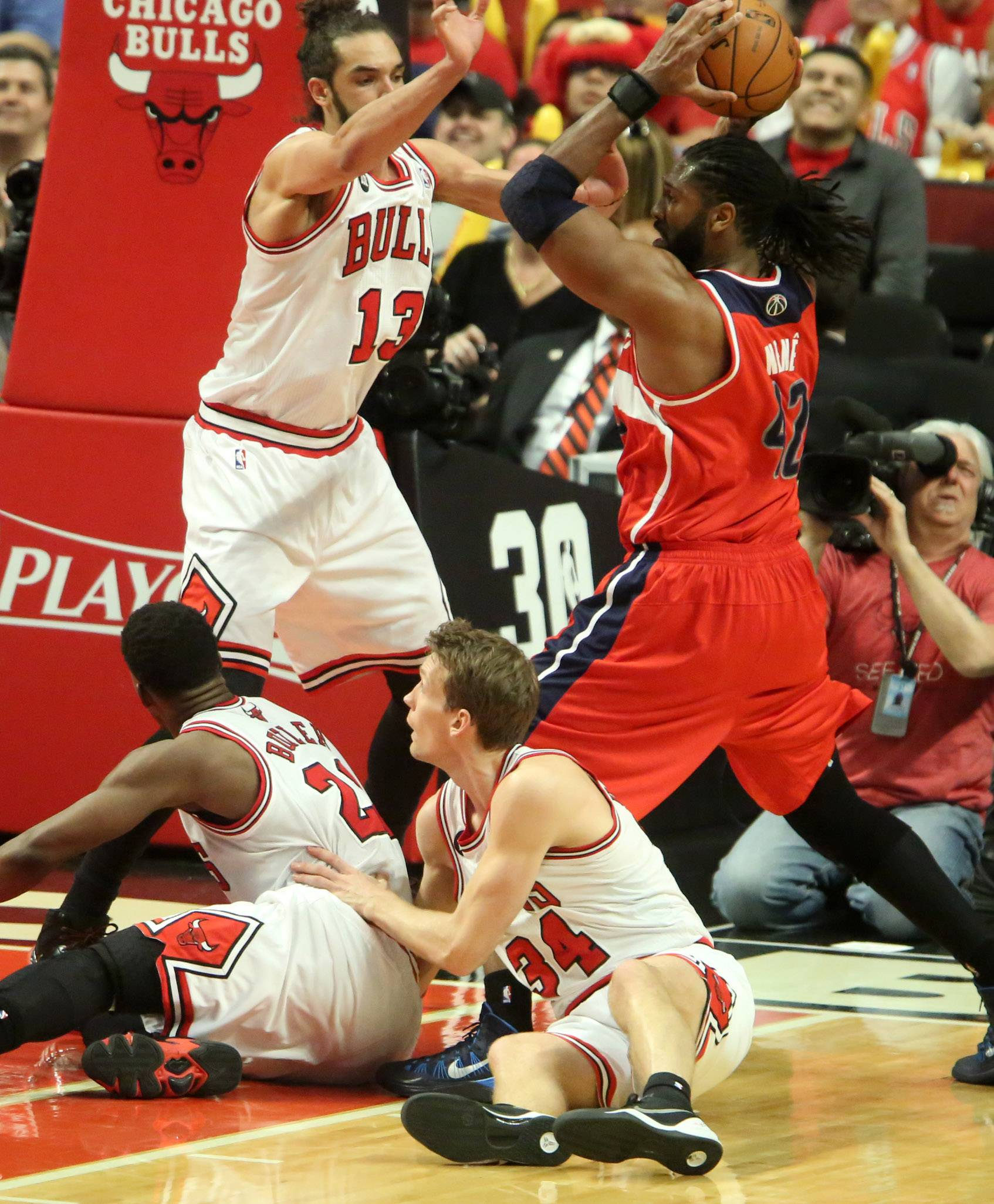 Bulls center Joakim Noah tries to block Washington Wizards forward Nene Hilario from passing in the second half of game 1 of an Eastern Conference first-round NBA playoff series on Sunday in Chicago.
