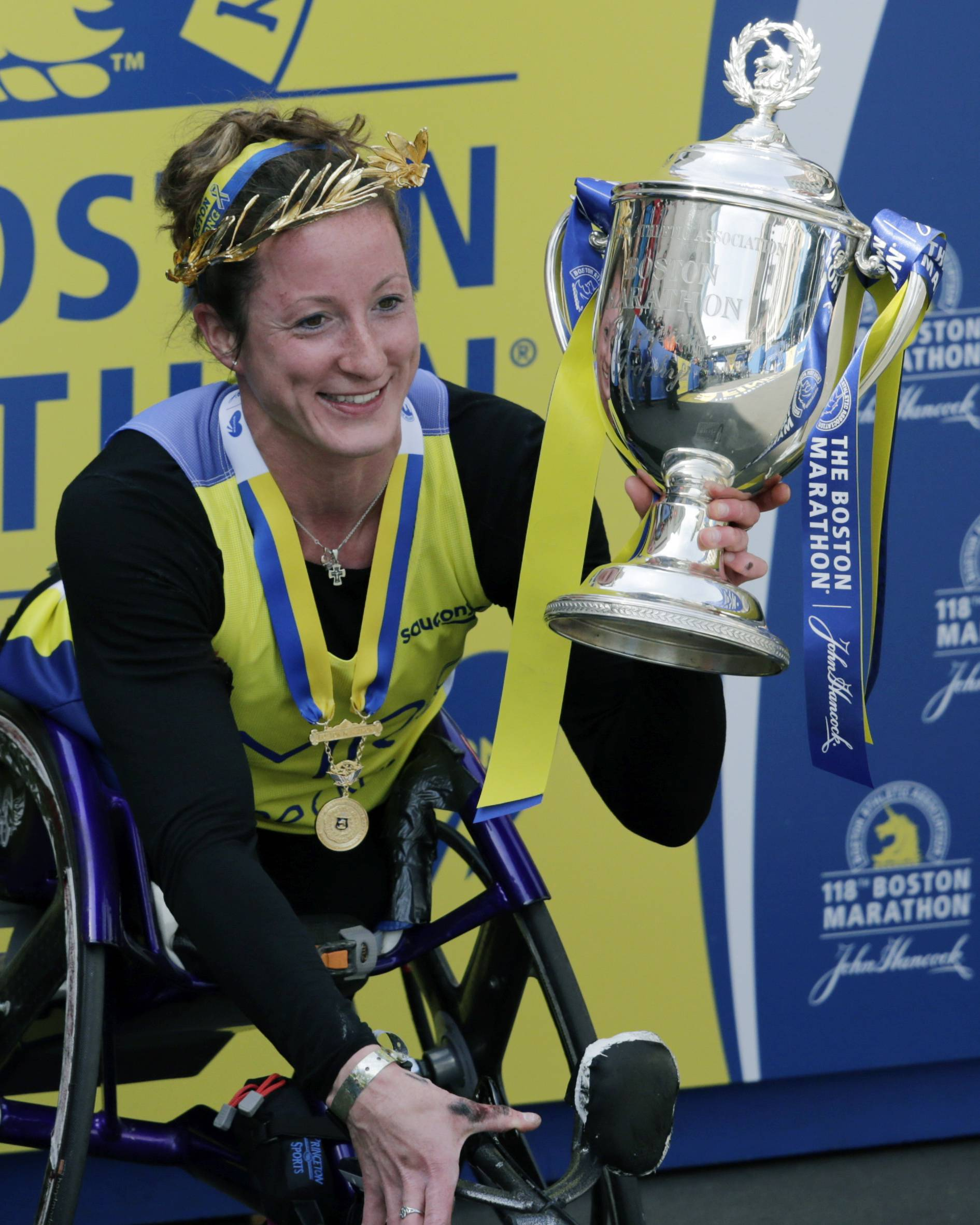 Tatyana McFadden, of the United States, displays her trophy after winning the women's wheelchair division of the 118th Boston Marathon Monday, April 21, 2014 in Boston.