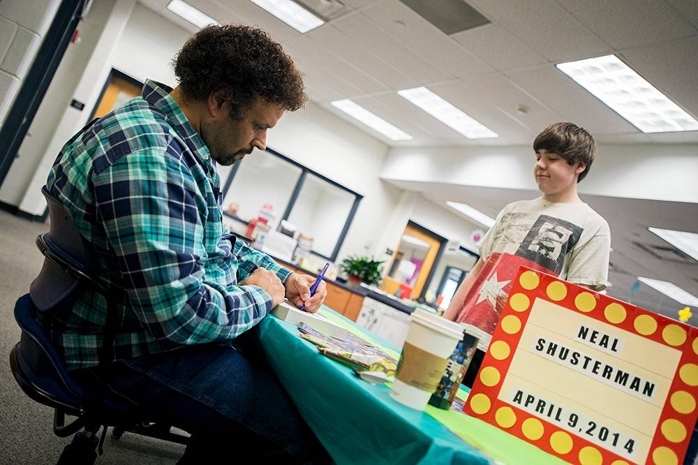 Neal Shusterman signs his book for a student at Grove Junior High School in Elk Grove Village. Shusterman met with students at Grove to talk about his experience as a writer.
