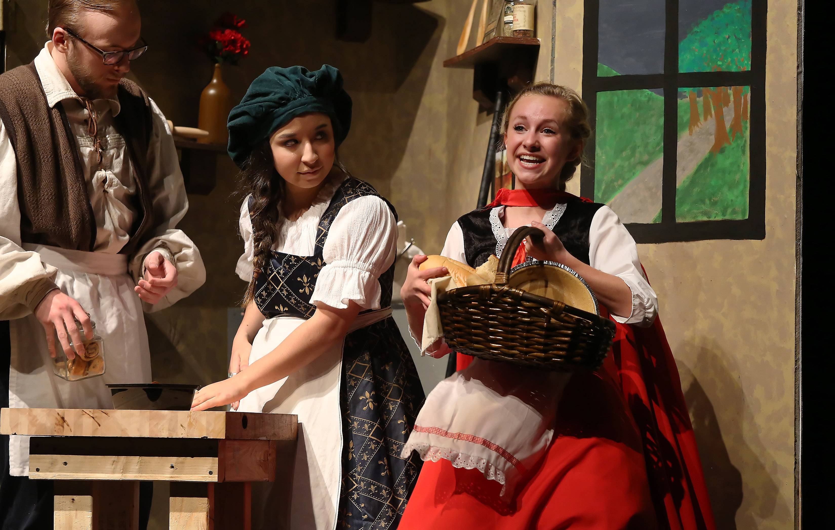 "Little Red Riding Hood, played by Anna Skelton, right, sings during a scene with the baker and his wife, played by Craig Hoeksema and Danielle Medina, during Tuesday's dress rehearsal of Warren Township High School's spring musical ""Into the Woods."" The production is Thursday through Saturday in the O'Plaine Auditorium in Gurnee."
