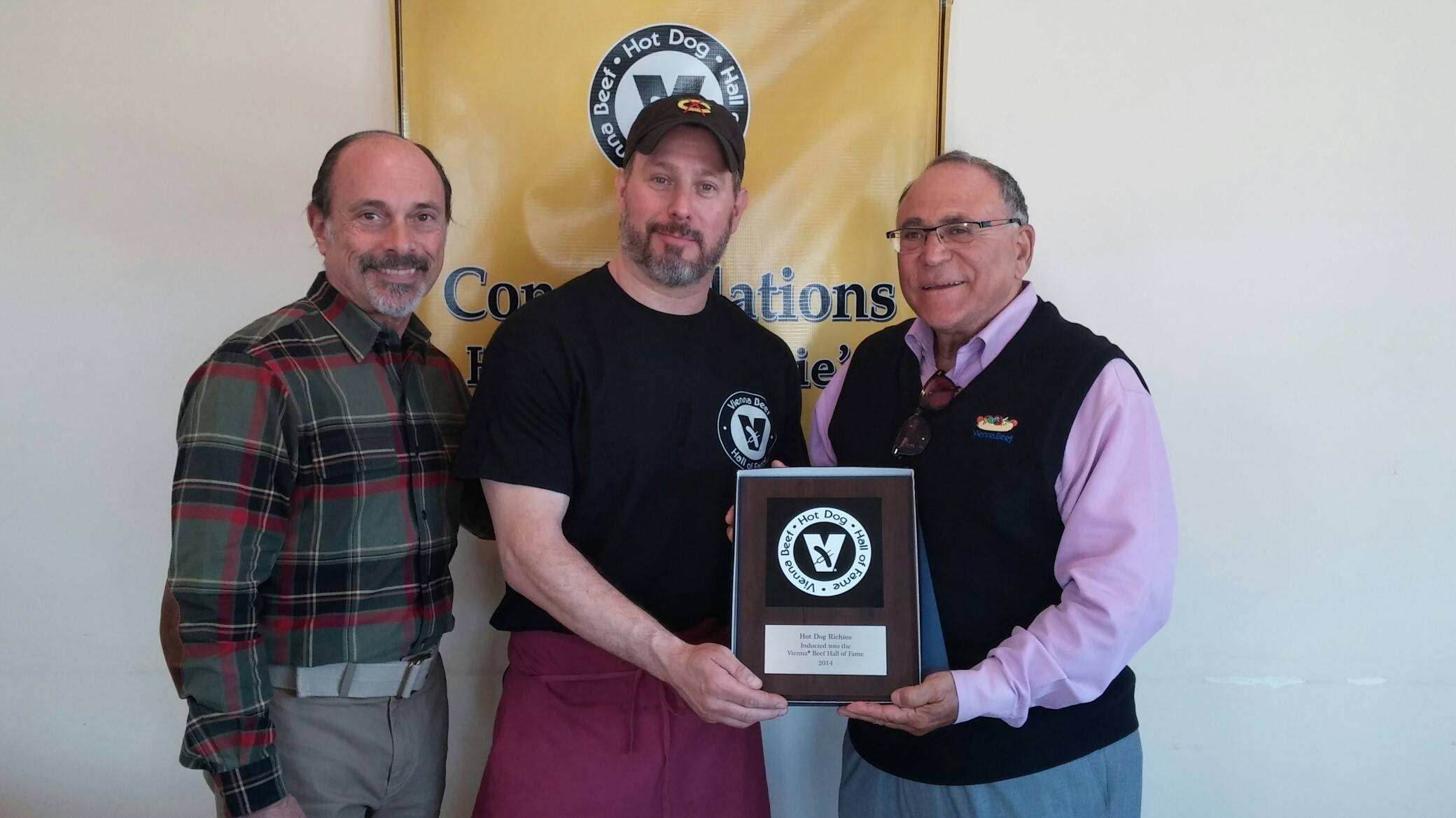 From left, Don Kaplan, Vienna Beef salesman, Jason Marzullo, Hot Dog Richie's owner, and Bob Schwartz, Vienna Beef senior vice president, pose with the plaque designating the Palatine restaurant as a member of the Vienna Beef Hot Dog Hall of Fame after an induction ceremony Tuesday morning.
