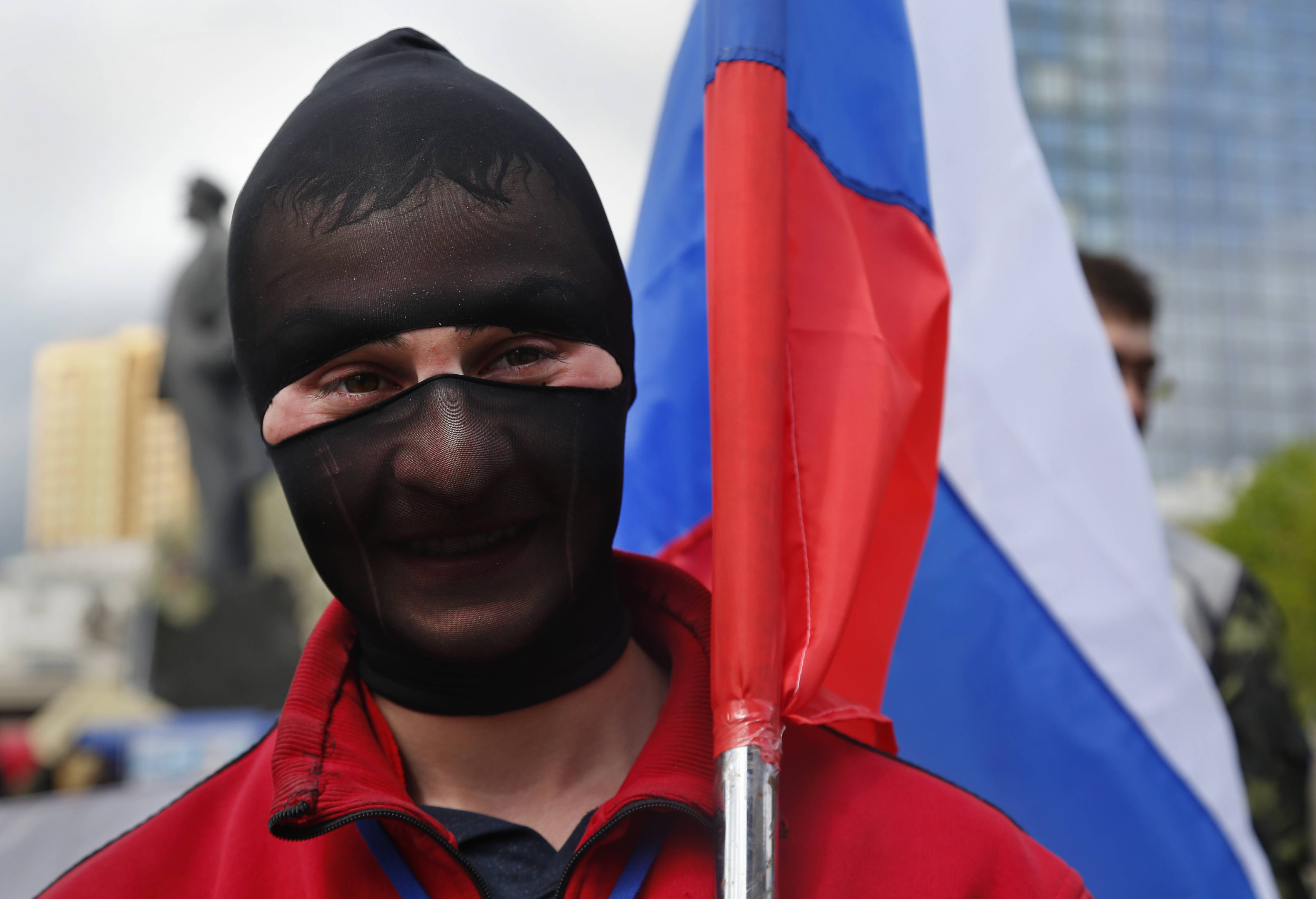 A pro Russian supporter with his face covered, holds a Russian flag in Donetsk, eastern Ukraine, Tuesday.