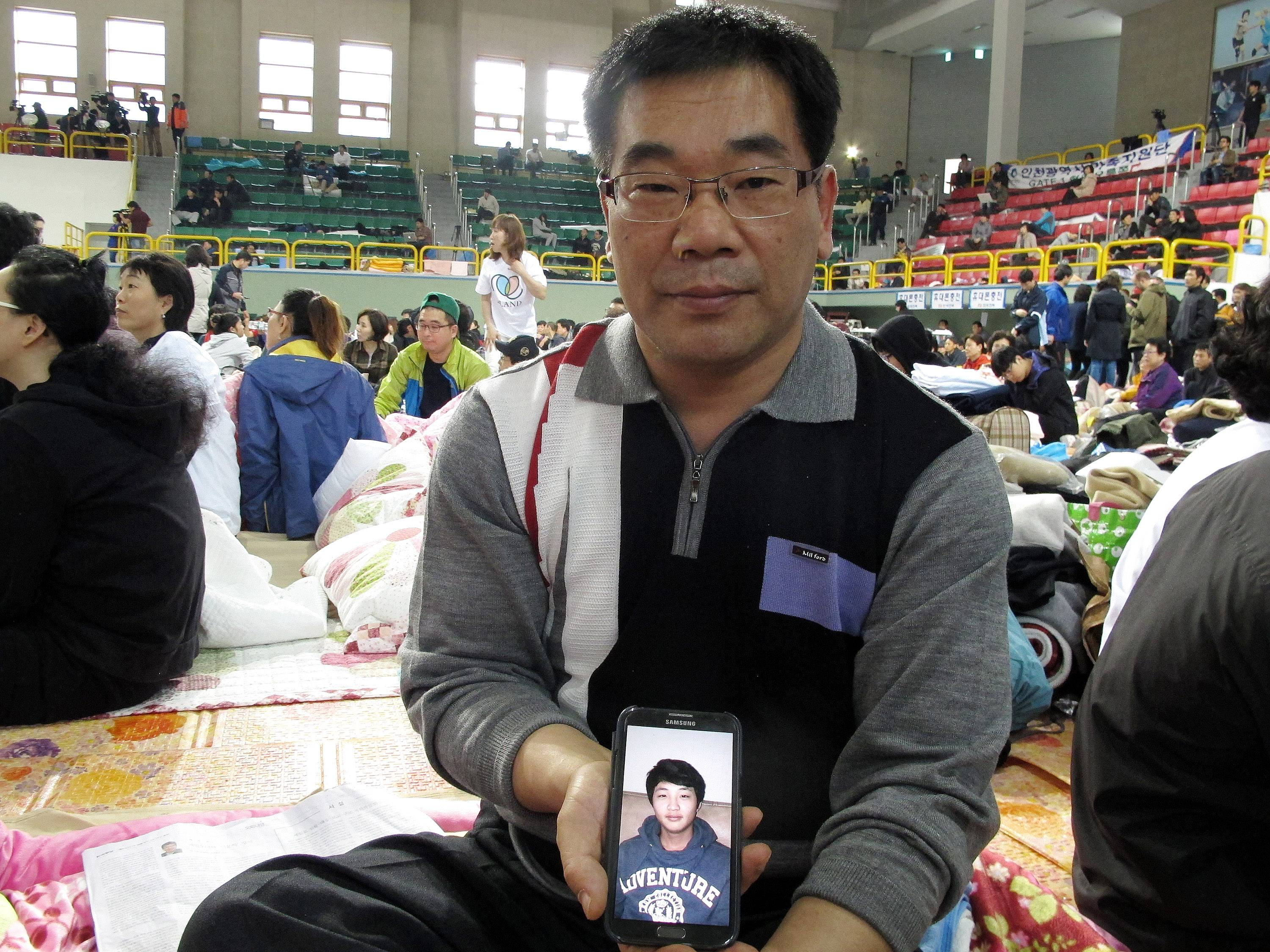 Lee Jong-eui shows a photograph of his nephew Nam Hyun-chul, one of missing passengers aboard the sunken ferry Sewol, during an interview at a gymnasium in Jindo, South Korea. Lee said 16-year-old Hyun-chul's parents poured their energy, love and attention into their only child. Though an overseas education is often pricey, his parents had sent him to school in New Zealand for a while.