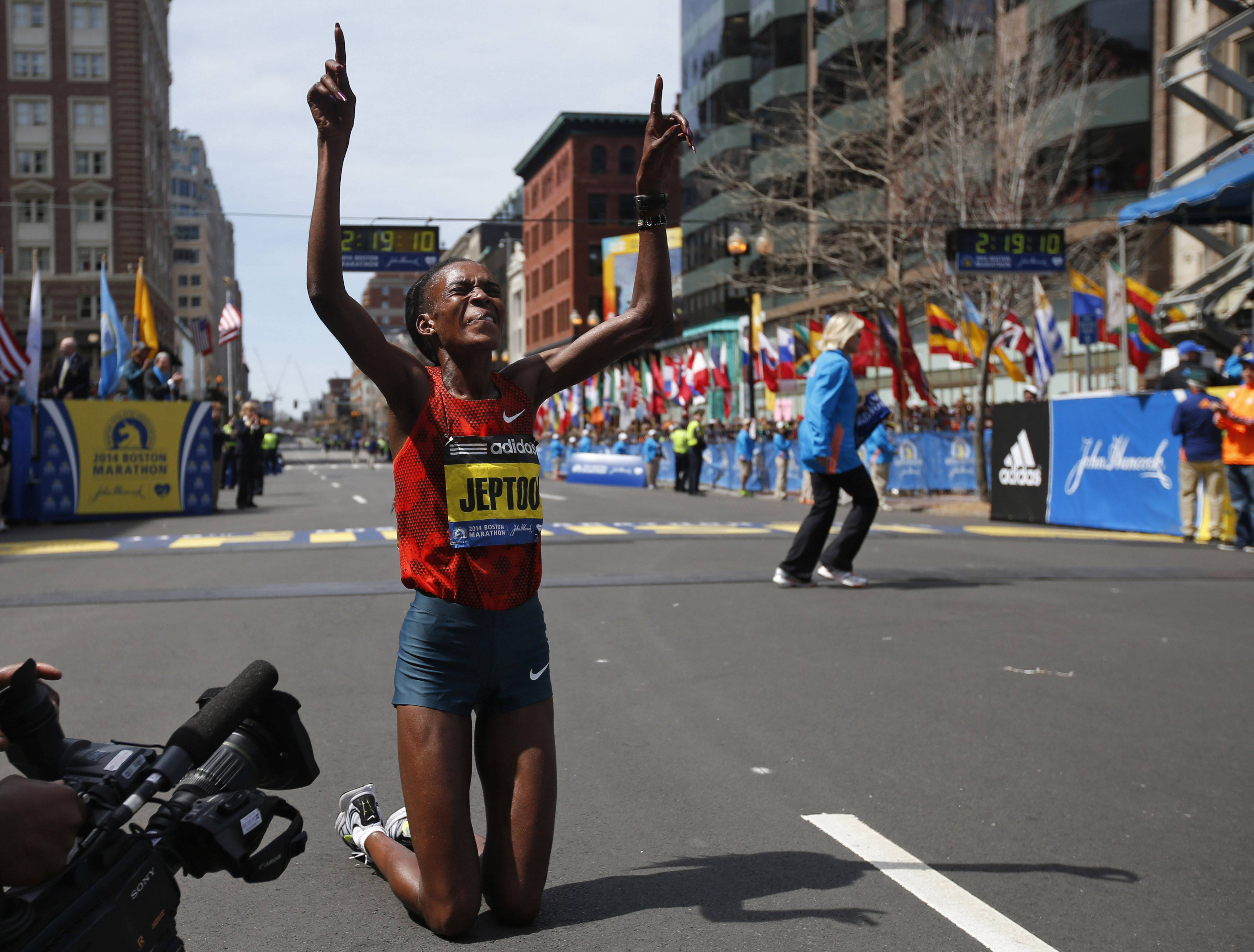 Rita Jeptoo, of Kenya, celebrates her win in the women's division of the 118th Boston Marathon Monday, April 21, 2014 in Boston.