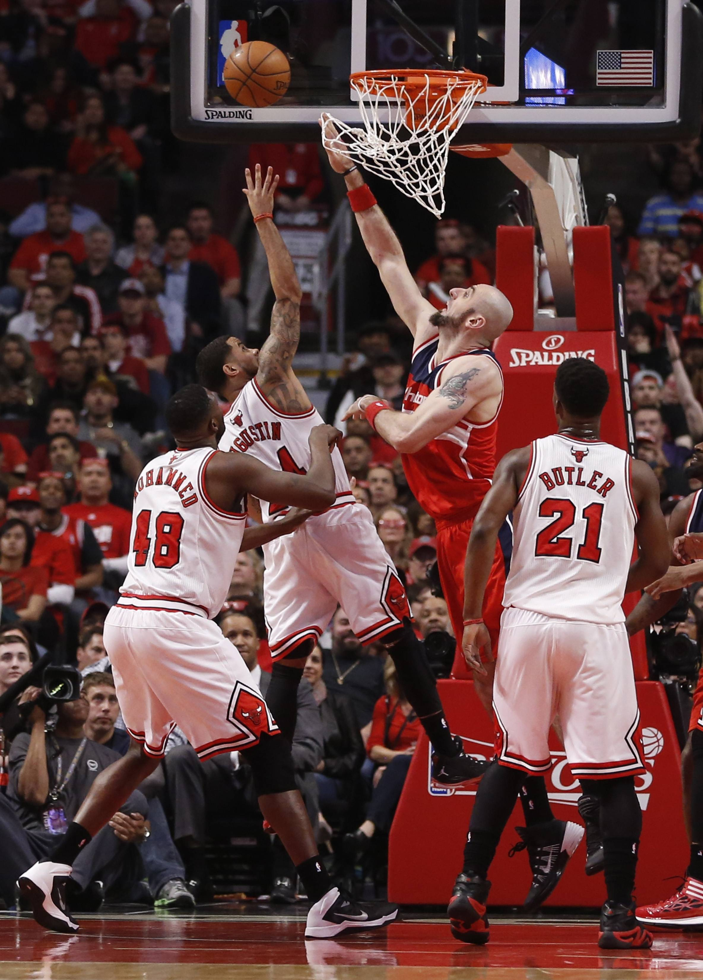 Chicago Bulls guard D.J. Augustin (14) shoots over Washington Wizards center Marcin Gortat (4) as Nazr Mohammed (48) and Jimmy Butler (21) watch during the first half of Game 2 in an opening-round NBA basketball playoff series Tuesday in Chicago.