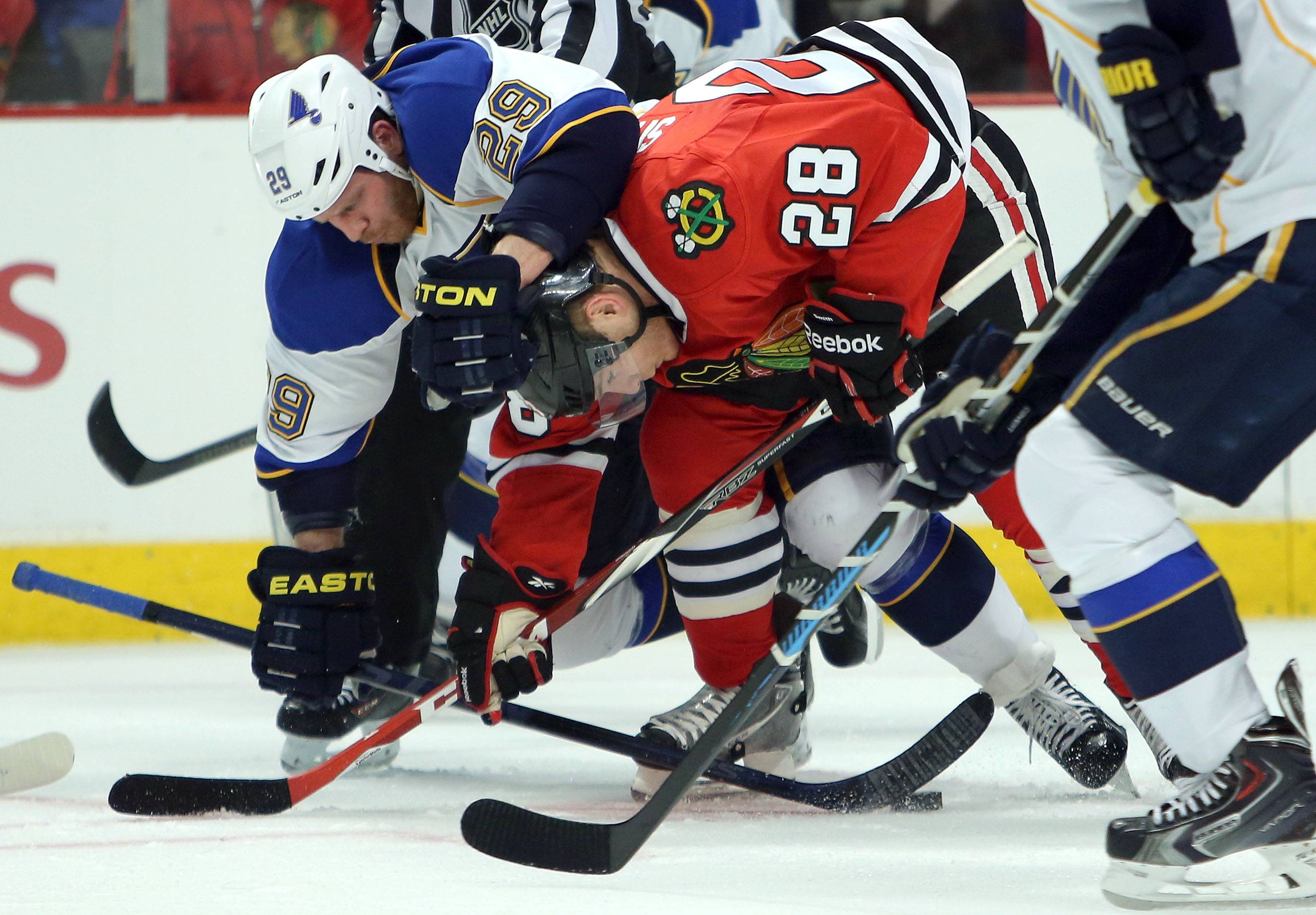 The Blues' Steve Ott and Ben Smith battle after a faceoff during the Hawks' 2-0 win in Game 3 at the United Center on Monday night.