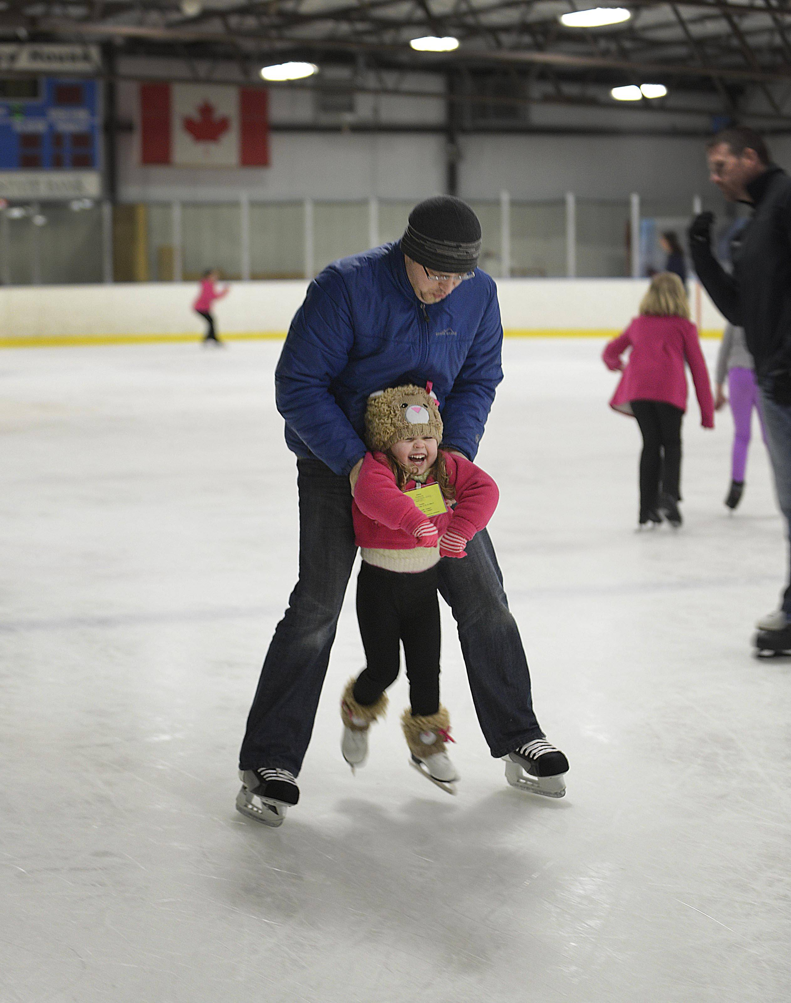 3-year-old Samantha Kay gets a lift from her dad, Vitali, of Cary, during a free skate period during a beginners skating class at Crystal Ice House.