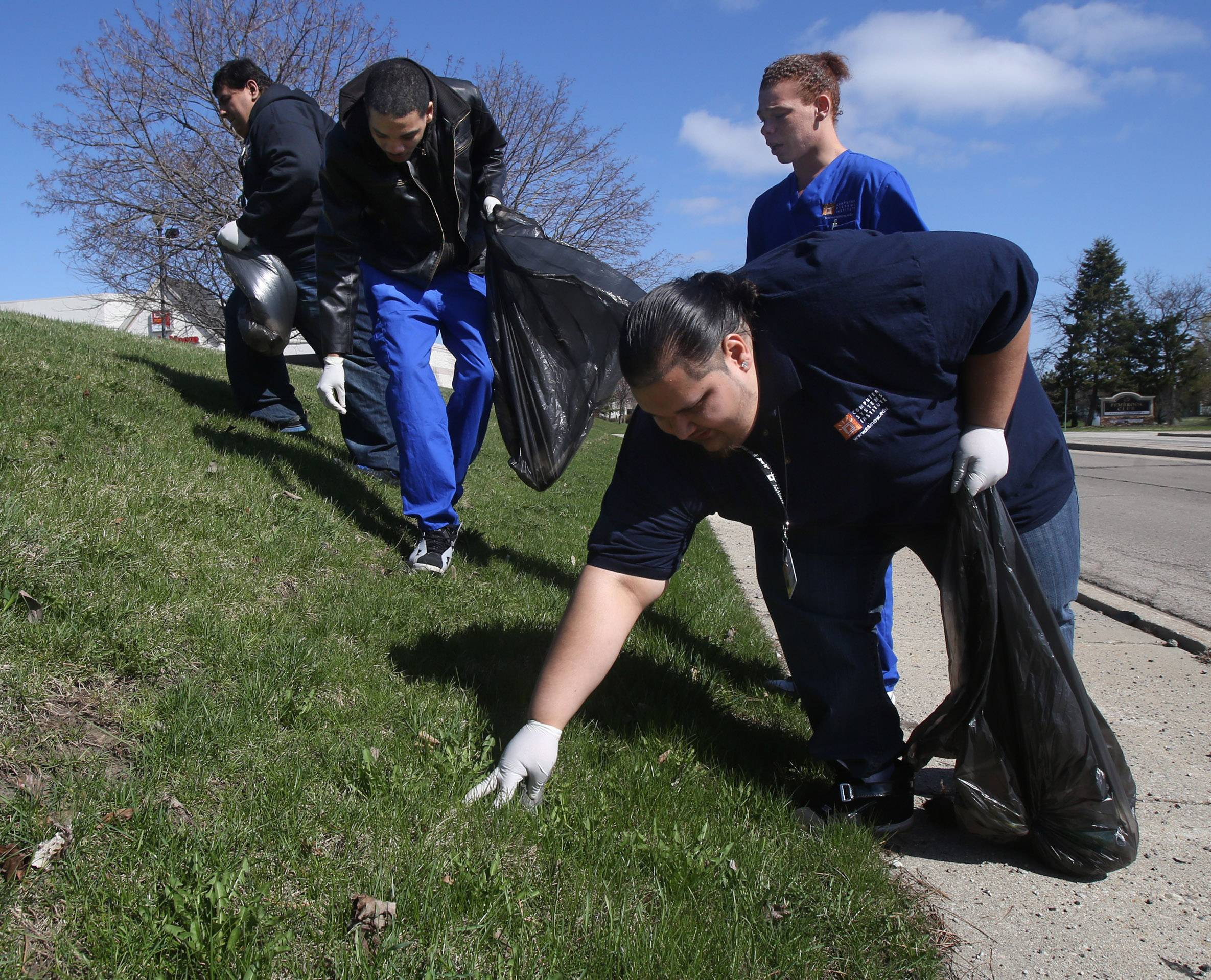 Miguel Hernandez, right, and other Computer Systems Institute students and faculty pick up trash along Lawson Boulevard in Gurnee on Tuesday for Earth Day. In the background are Angel Perez, left, Eddie Evans and Troy Clark.