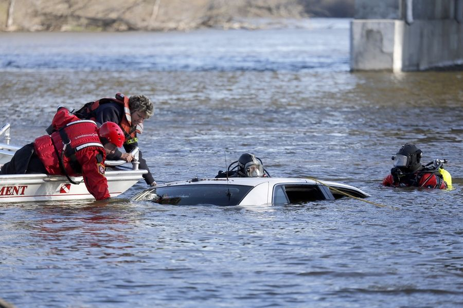 South Elgin firefighter Burt Lancaster, from left, Elgin Fire Department Lt. Amanda Bruce, and divers Randy Freise and Steve Wascher, from the Elgin and South Elgin fire departments, respectively, attempt to hook up a car that was located Tuesday in the Fox River near Interstate 90 in Elgin.