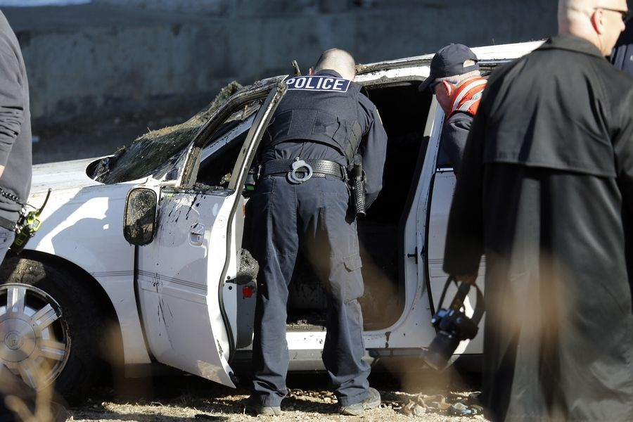 Police officers search a car Tuesday after it was removed from the Fox River in Elgin.