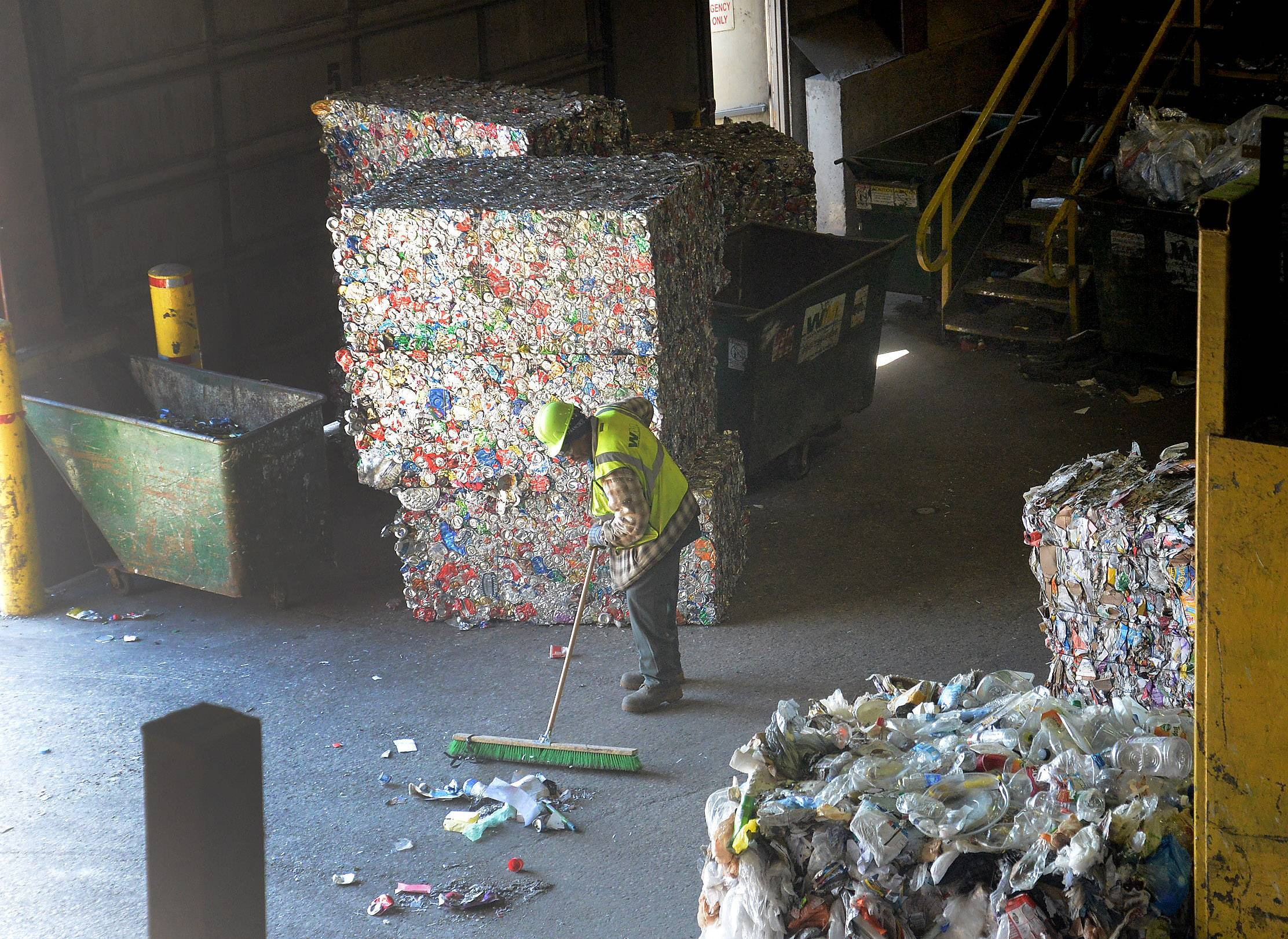 A man sweeps up at the Waste Management recycling facility in Grayslake.
