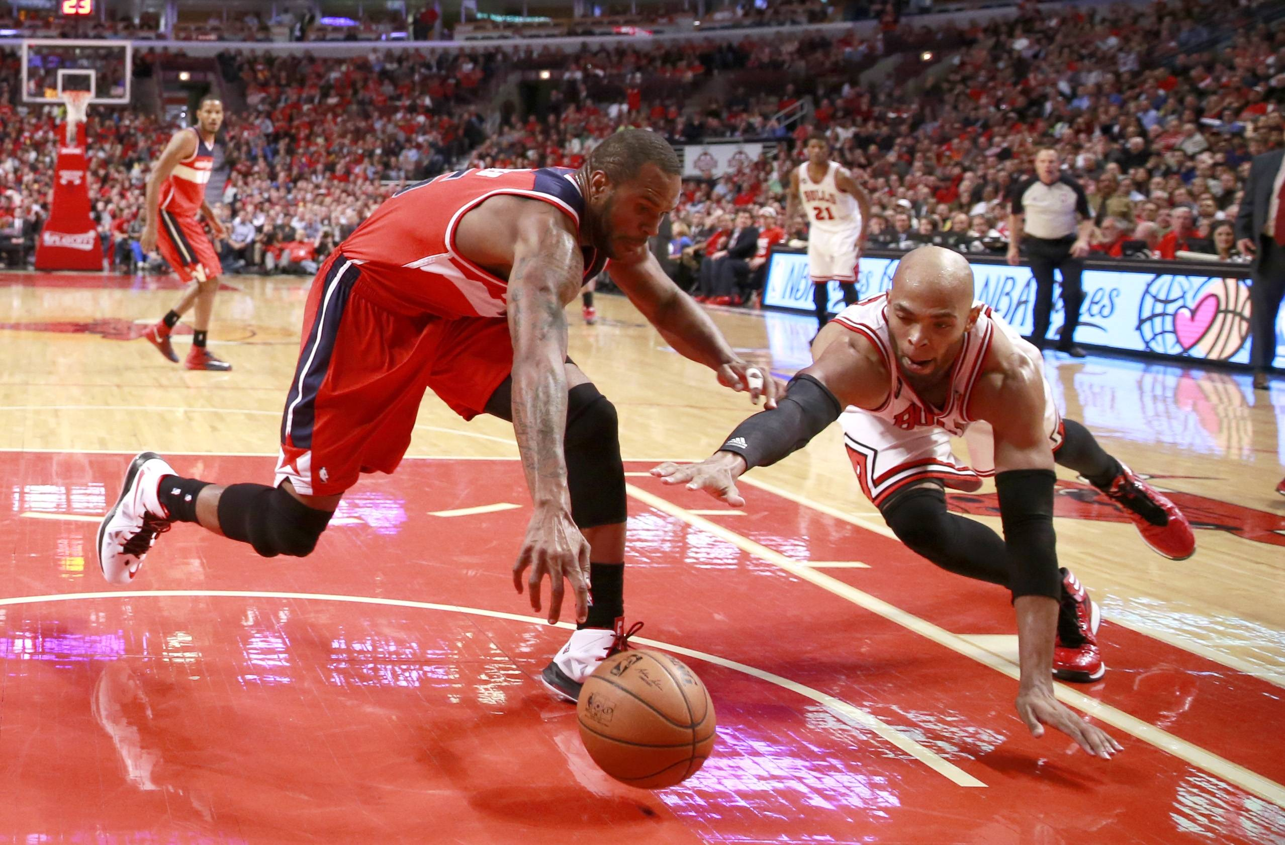 Washington Wizards forward Trevor Booker, left, and Bulls forward Taj Gibson scramble for a loose ball during the second half of Game 2 Tuesday in Chicago. The Wizards won 101-99.