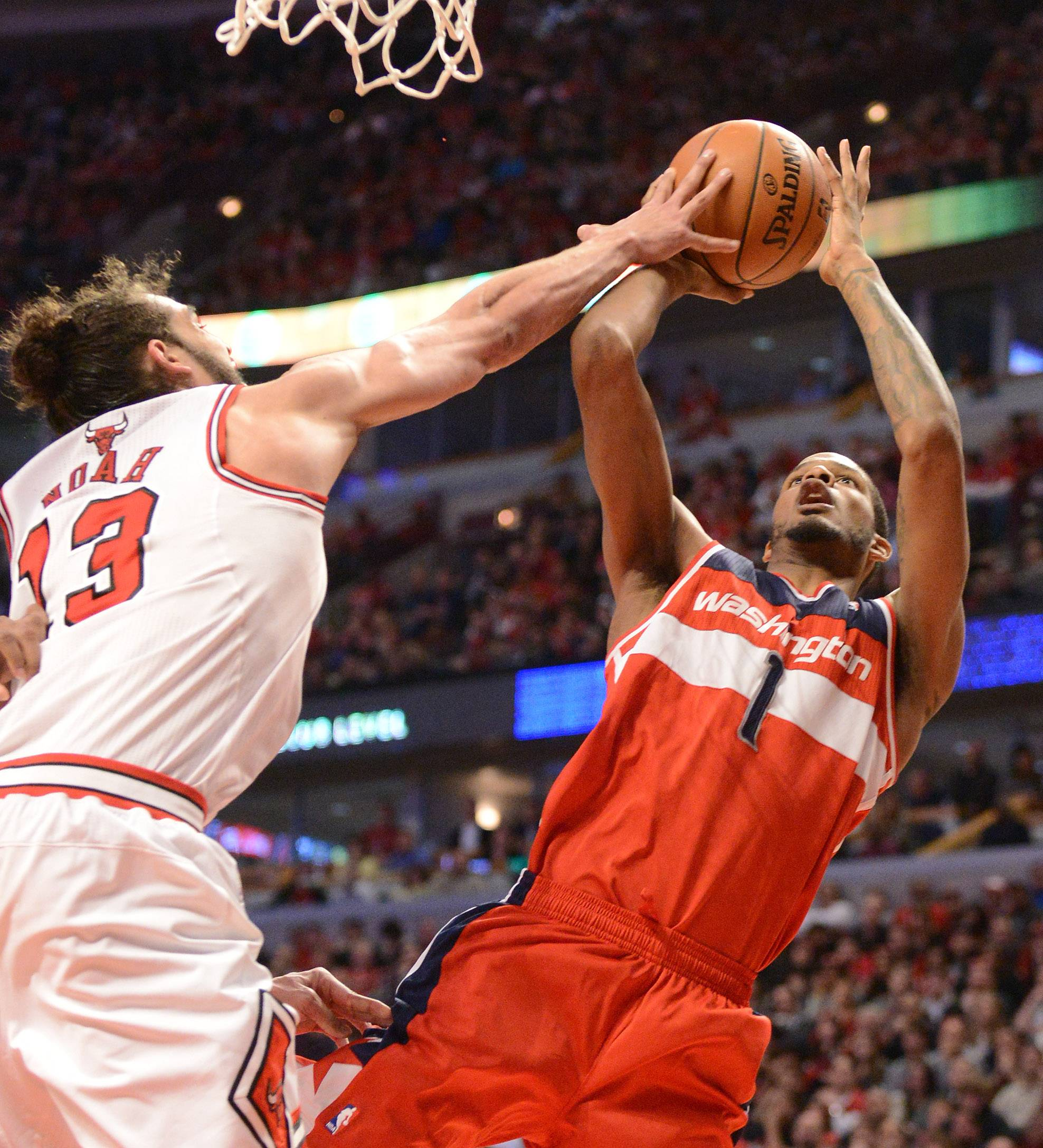 Chicago Bulls center Joakim Noah (13) gets a hand on a shot by Washington Wizards forward Trevor Ariza (1).