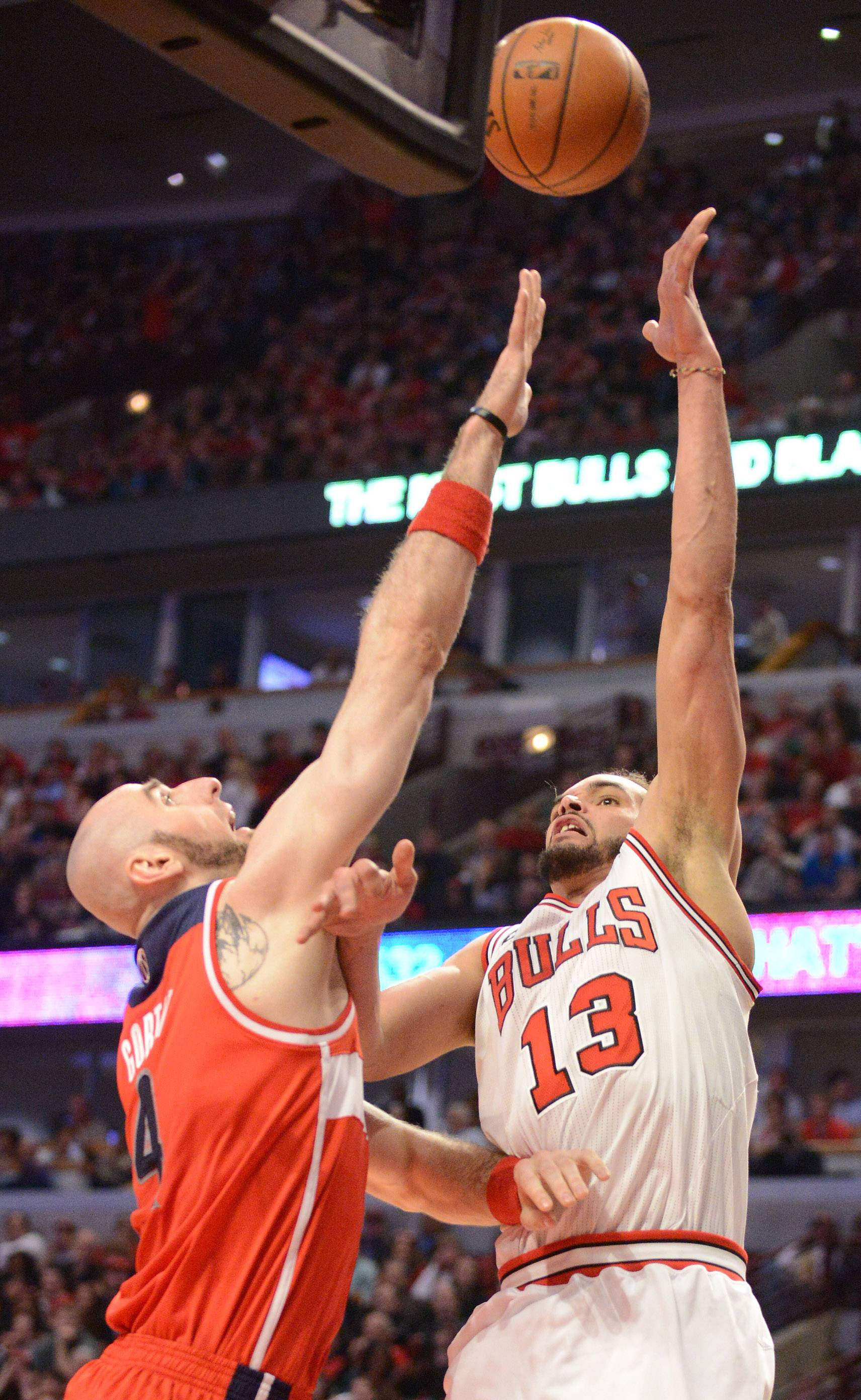 Chicago Bulls center Joakim Noah (13) shoots and scores over Washington Wizards center Marcin Gortat (4).