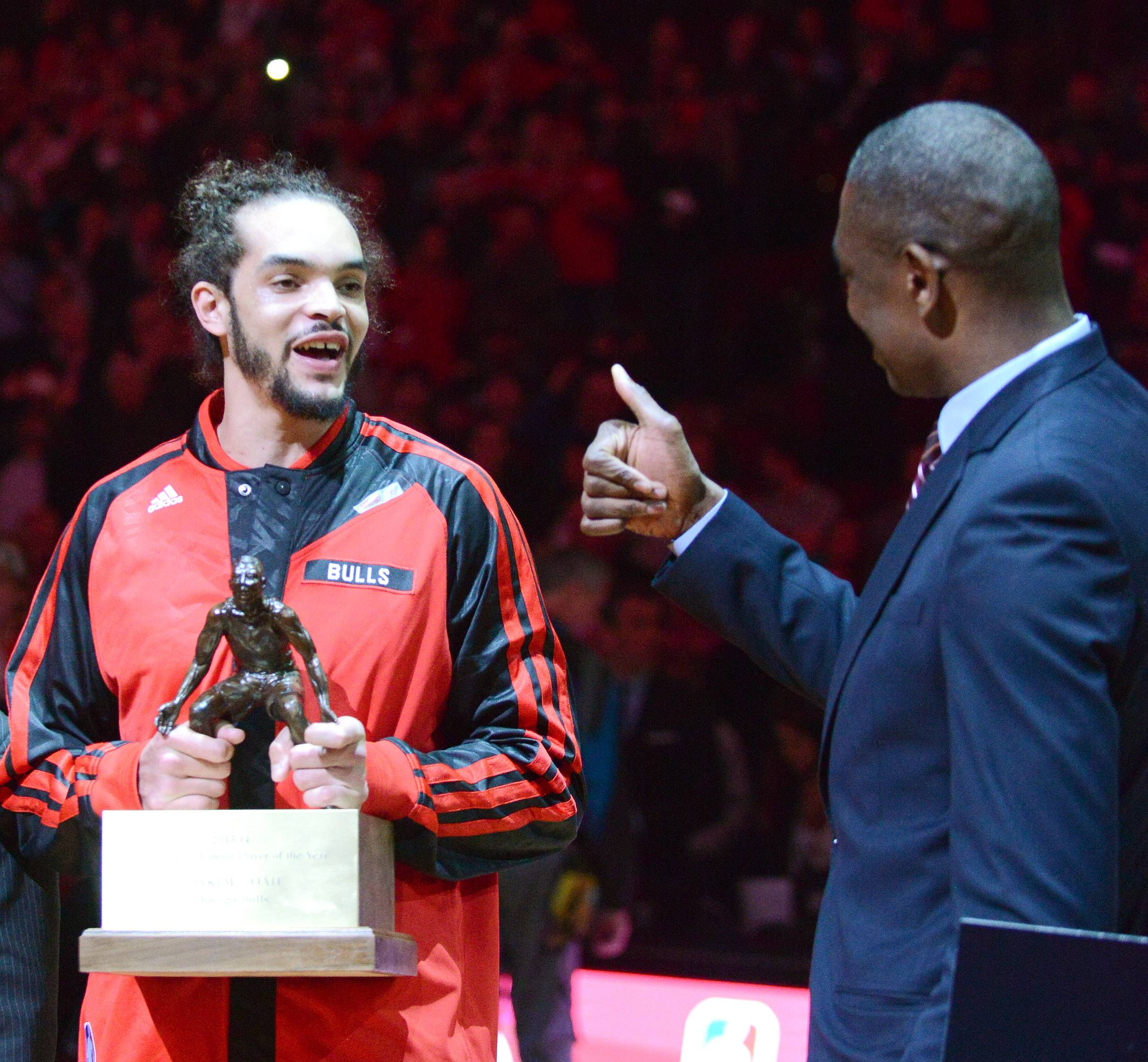 Chicago Bulls center Joakim Noah (13) gets a thumbs up from Dikembe Mutombo  after receiving the Defensive Player of the Year award before Tuesday's game at the United Center in Chicago.