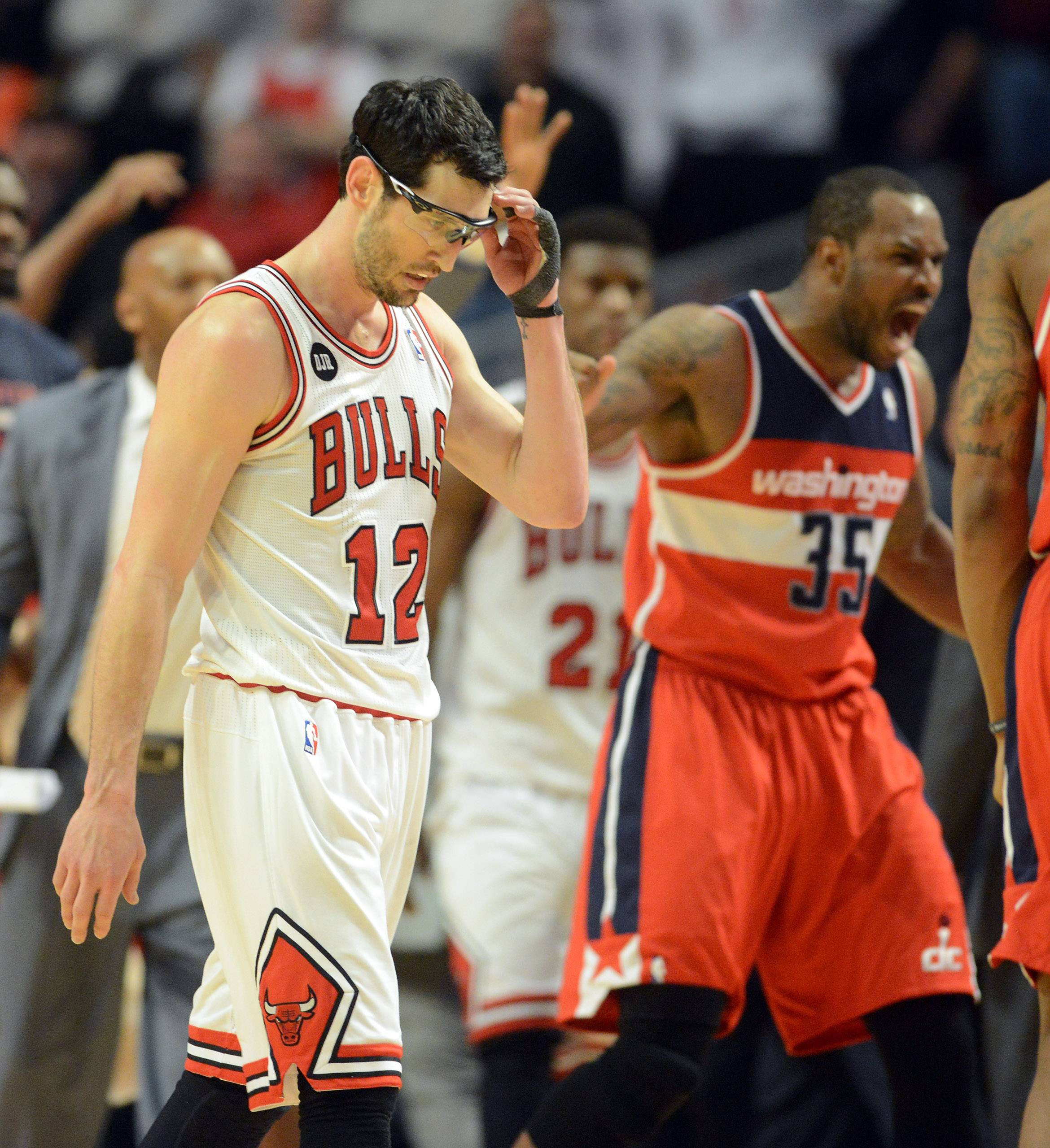 Chicago Bulls guard Kirk Hinrich (12) walks off the court as Washington Wizards forward Trevor Booker (35) celebrates after Hinrich missed a chance to tie the game with 2 free throws in overtime.