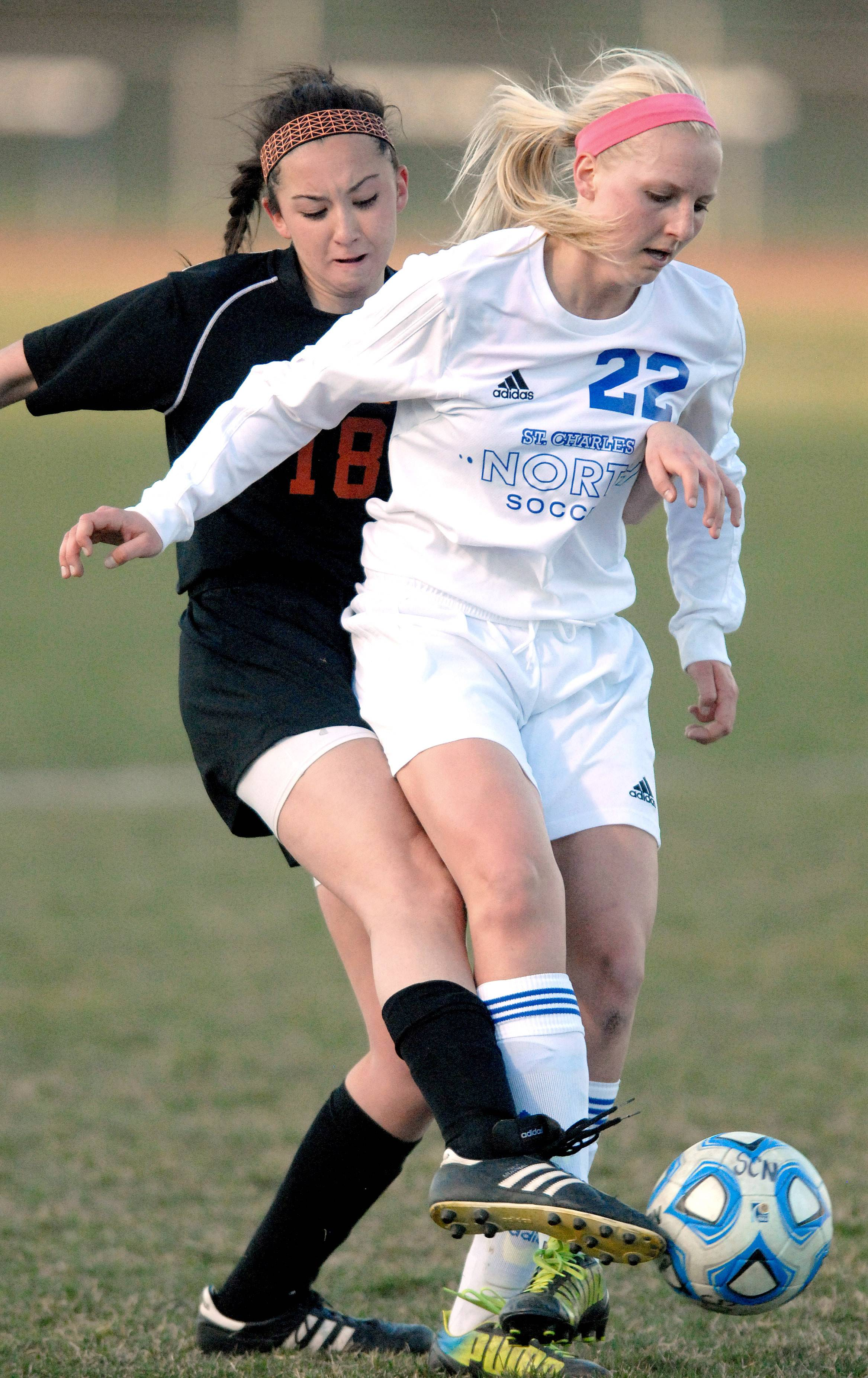 St. Charles East's Mallory Mollenhauer, left, and St. Charles North's Sophie Pohl fight for the ball in the first half on Tuesday.