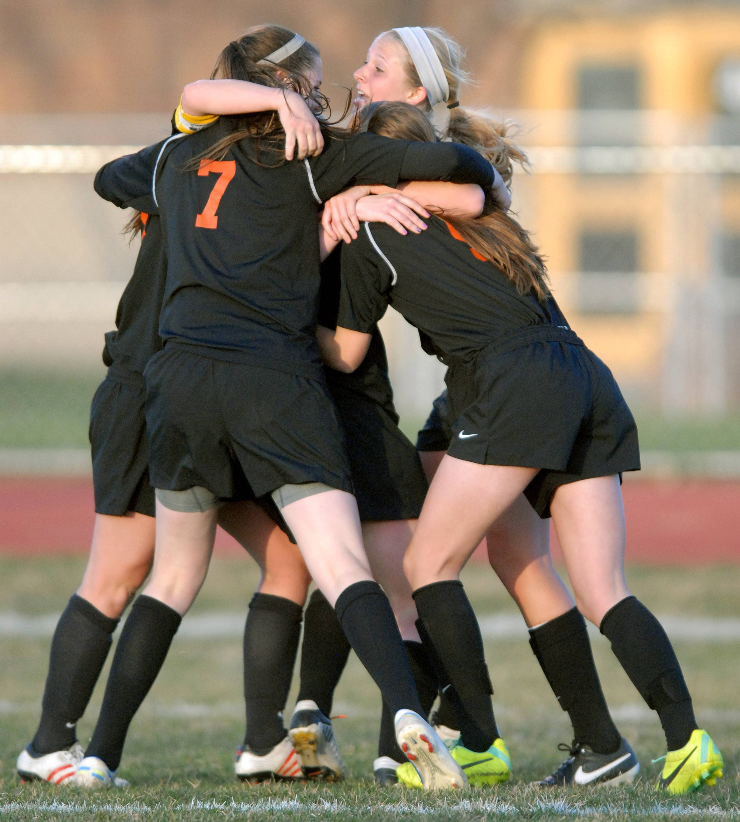 St. Charles East teammates swarm together after scoring a goal over St. Charles North in the first half on Tuesday, April 22.