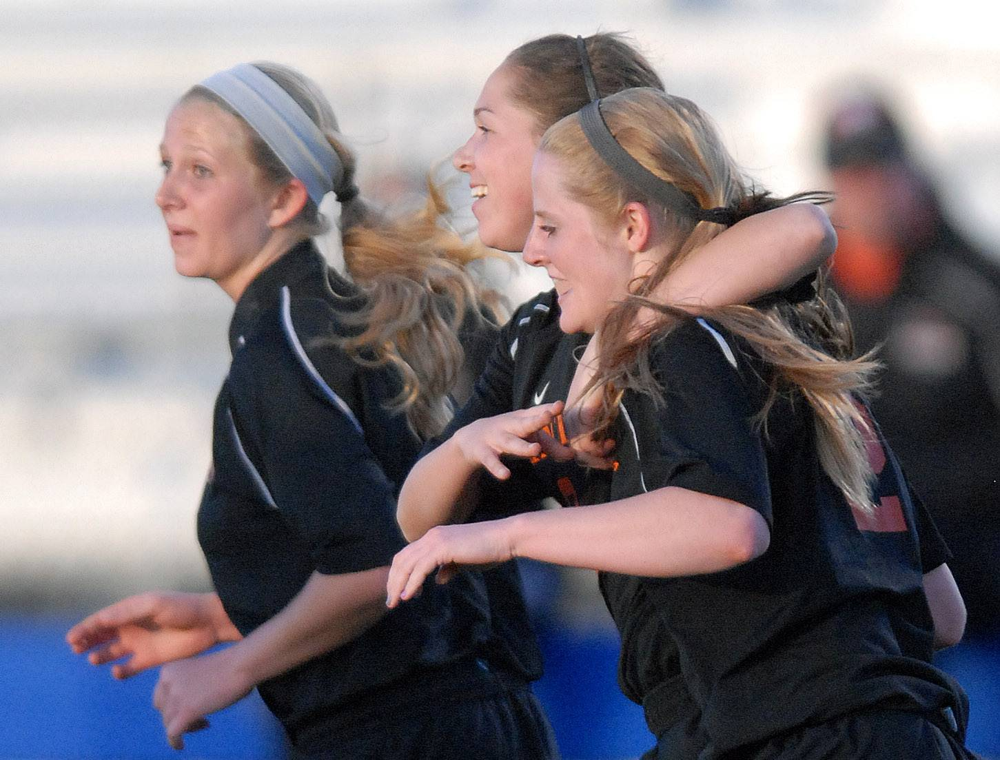St. Charles East's Darcy Cunningham, center, wraps her arm around teammate Julia Peterson as she celebrates scoring a goal in the first half on Tuesday, April 22.