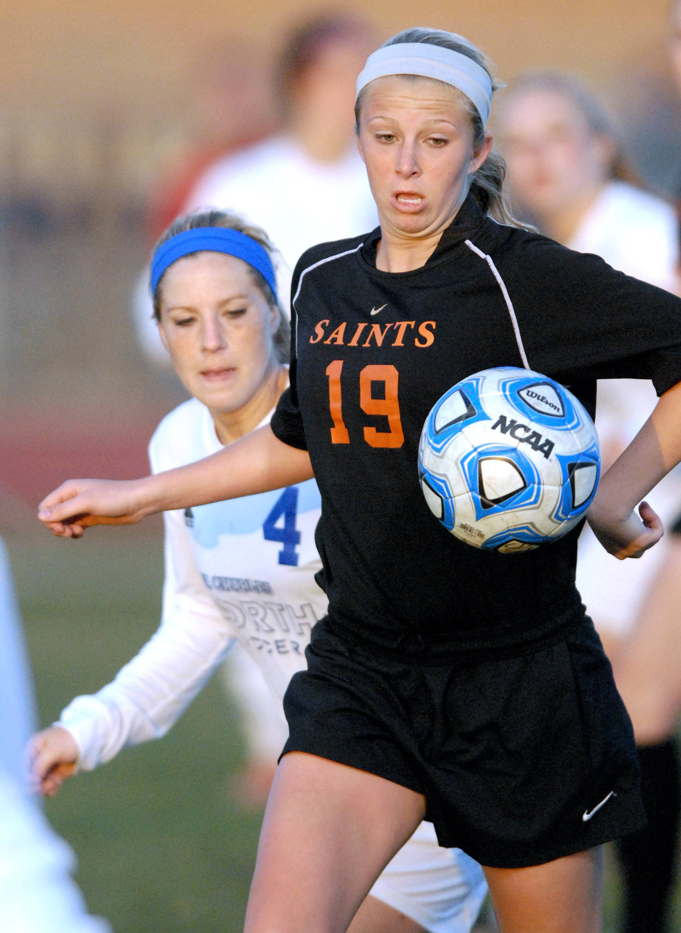 St. Charles North's Jenny Barr, left, trails St. Charles East's Sophie Jendrzeczyk as she gains control of the ball in the first half on Tuesday, April 22.