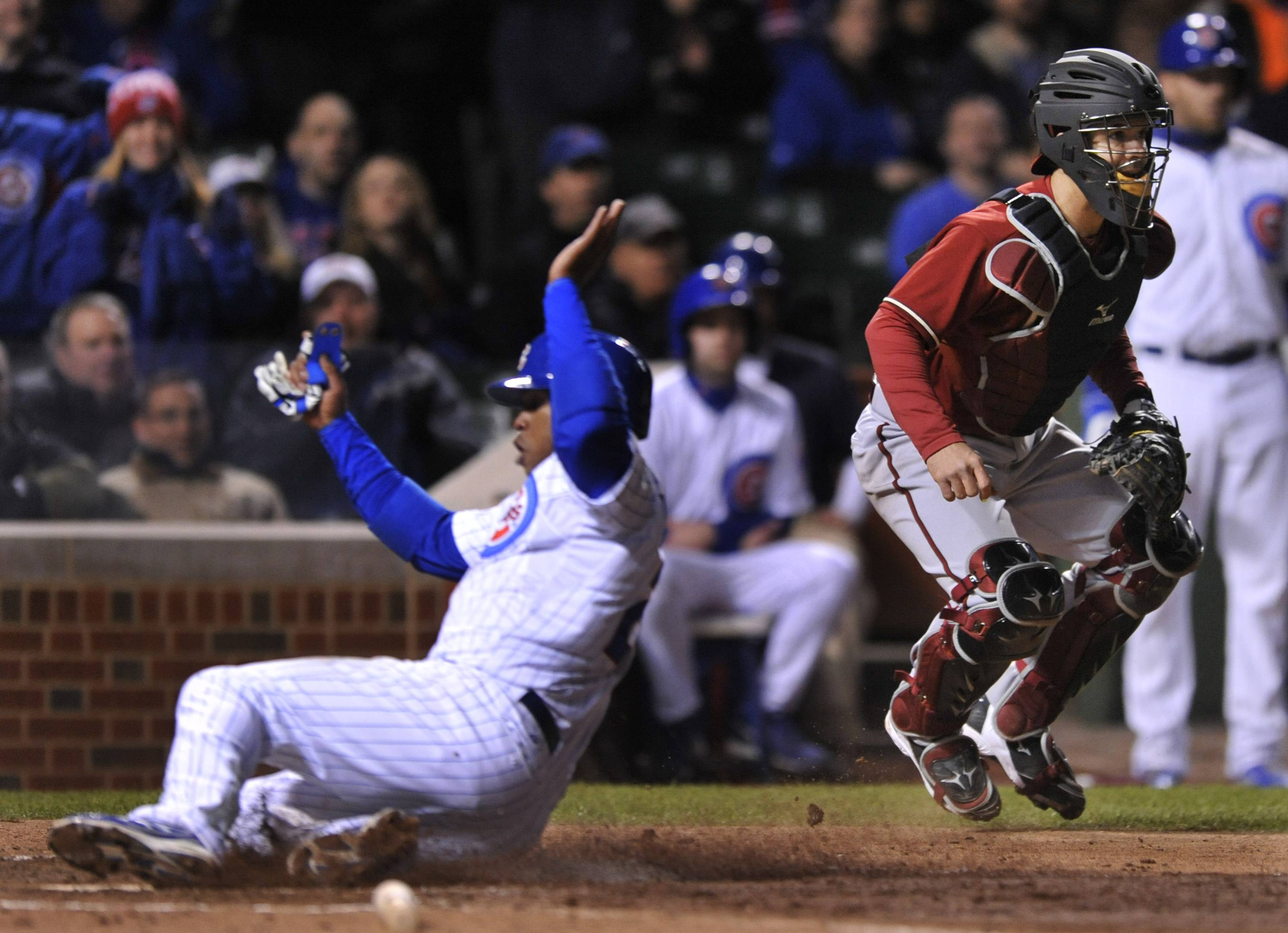 The Cubs' Luis Valbuena slides safely into home plate on a sacrifice fly as the ball rolls away from Diamondbacks catcher Tuffy Gosewisch in the fifth inning Tuesday at Wrigley Field.