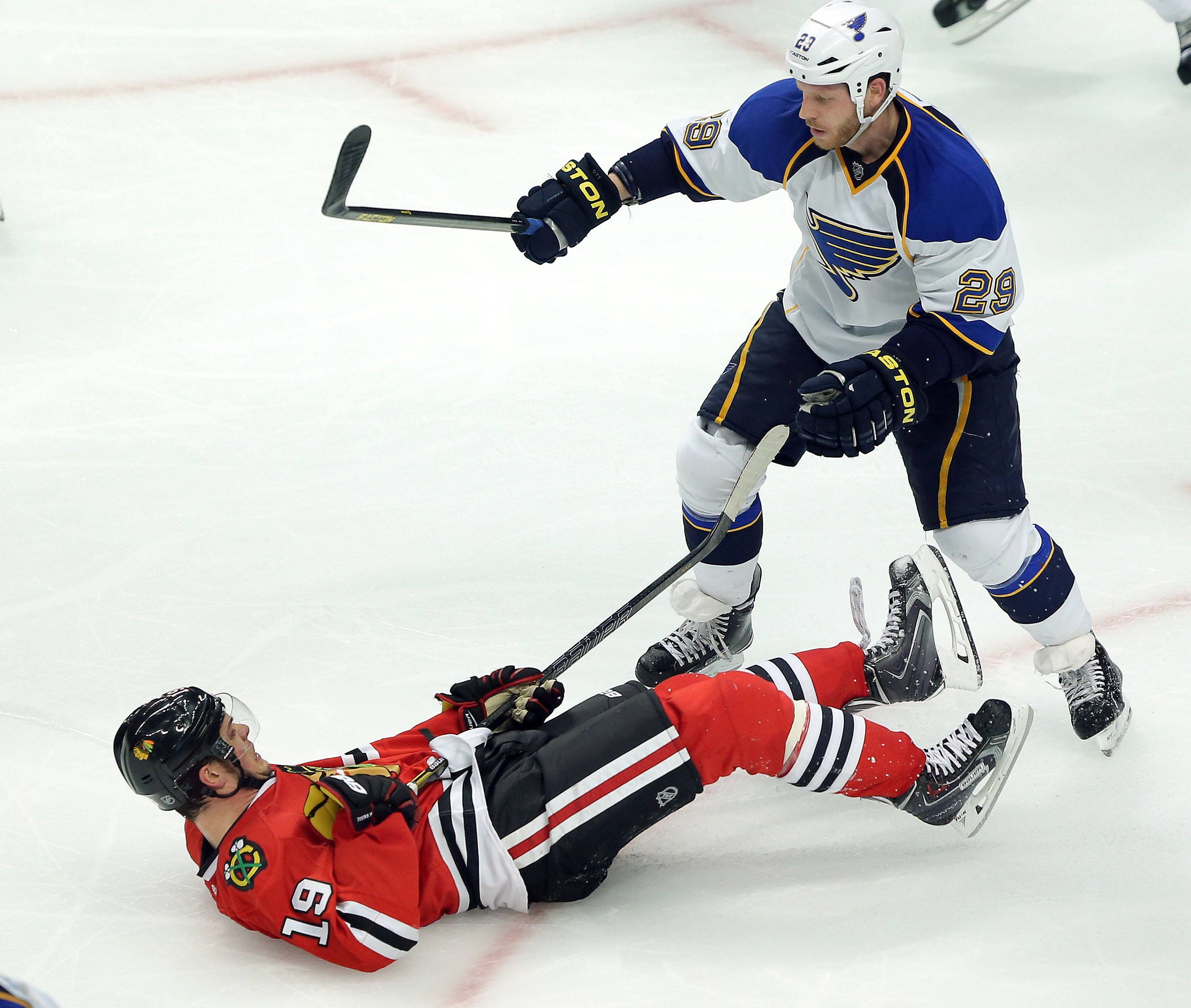 Jonathan Toews is sent sprawling by the Blues' Steve Ott during the Hawks' 2-0 win in Game 3 at the United Center on Monday night.