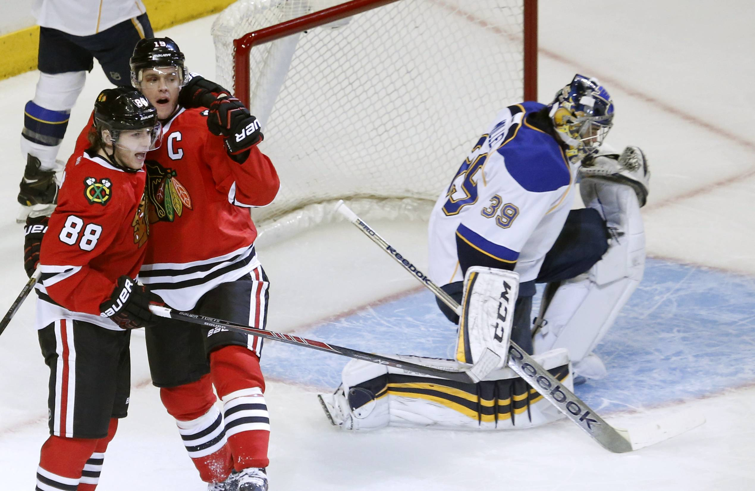 Chicago Blackhawks center Jonathan Toews, a second from left, celebrates his goal with Patrick Kane next to St. Louis Blues goalie Ryan Miller during the first period in Game 3 of a first-round NHL hockey Stanley Cup playoff series game Monday in Chicago.