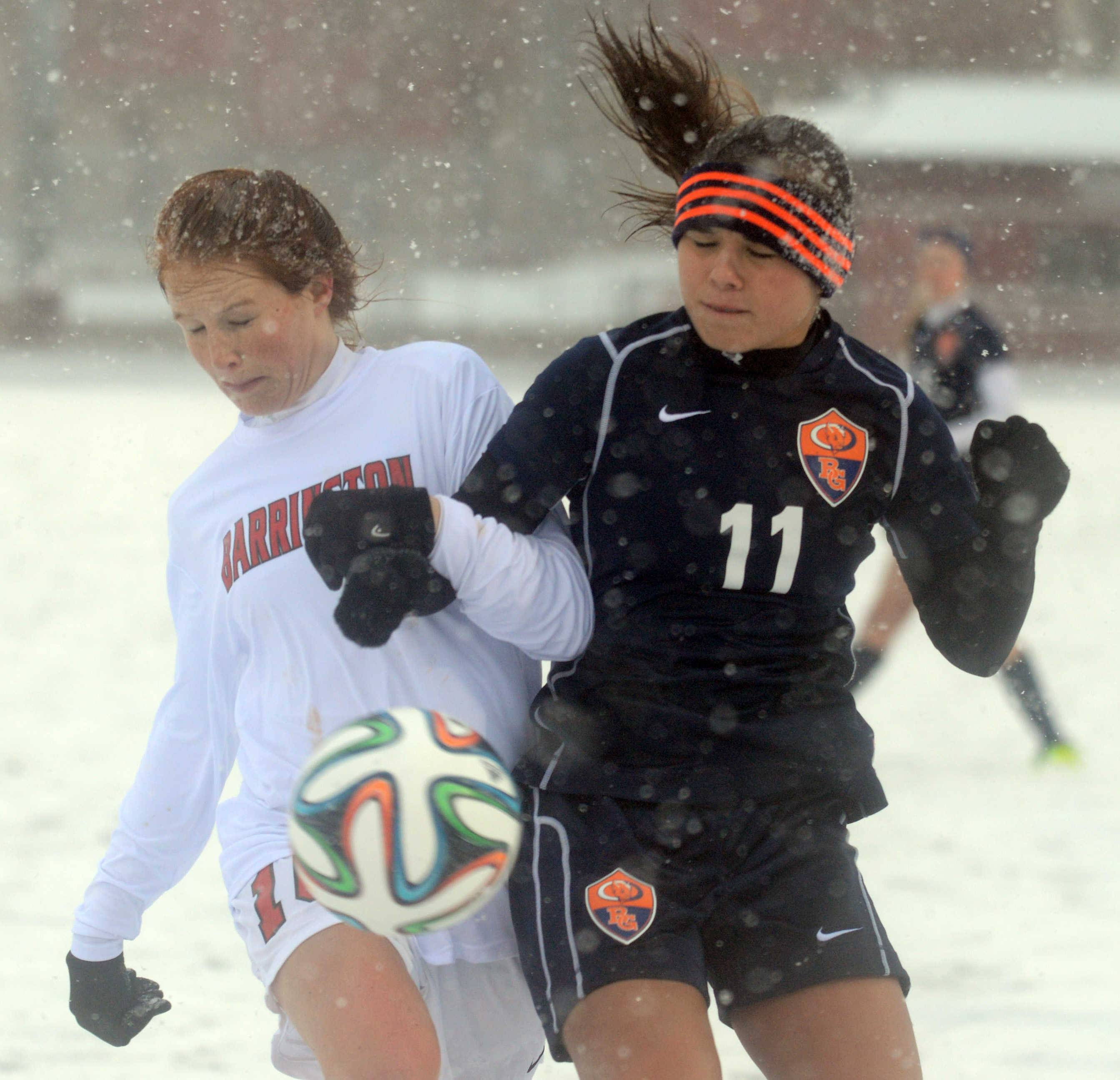 Barrington's Carrie Madden, left, gets tangled up with Buffalo Grove's Kim Herzog as they battle for the ball in the snow during Monday's soccer match in Barrington.