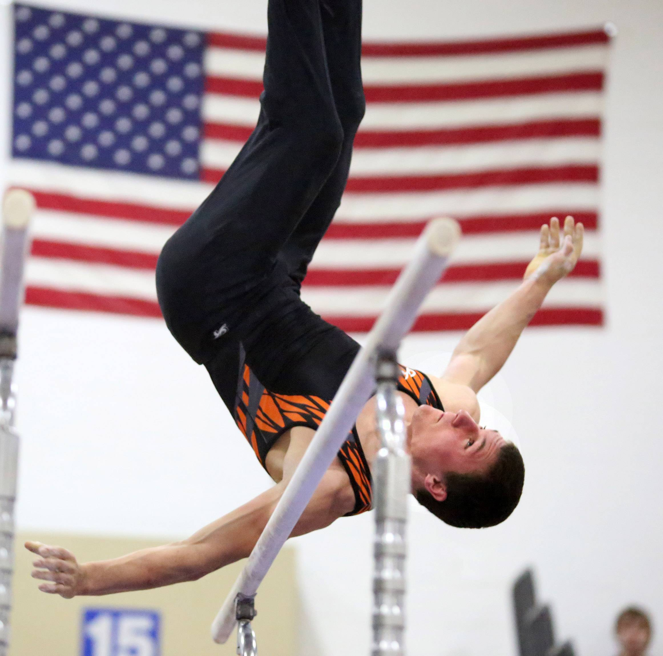 Libertyville's Jack Burke dismounts from the parallel bars during Thursday's gymnastics meet in Hoffman Estates.