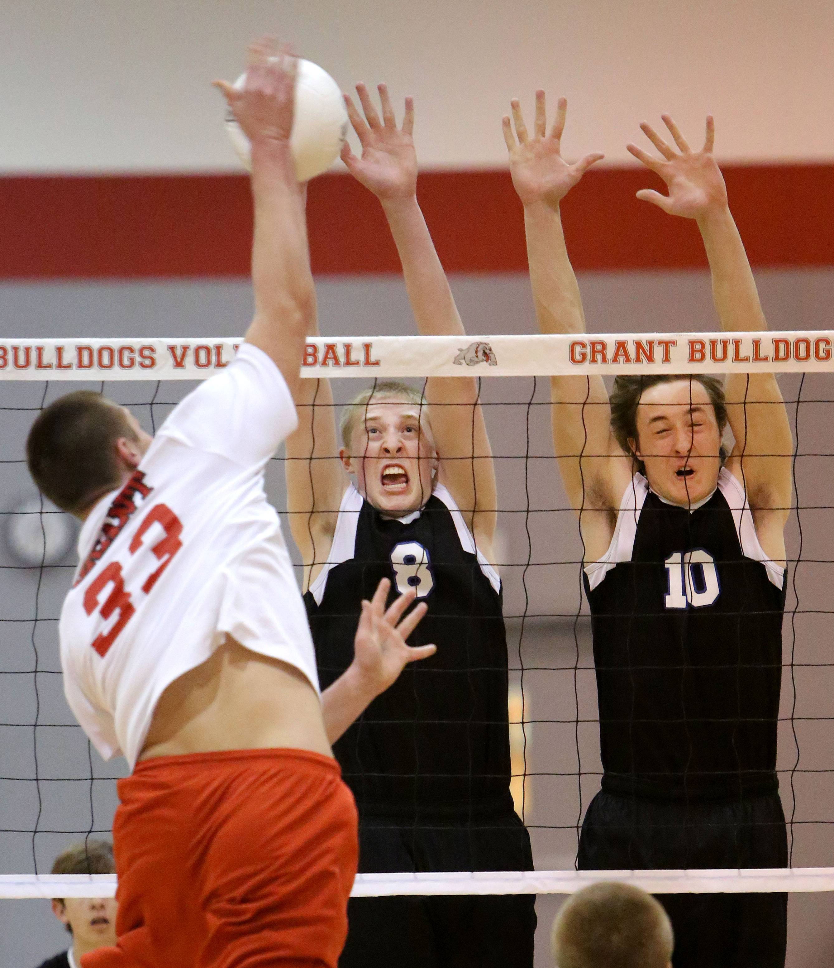 Grant's Brock Lundman, left, spikes one at Lake Zurich's Andrew Gilbertson and Brent Sweetwood during Monday's volleyball match in Lake Zurich.