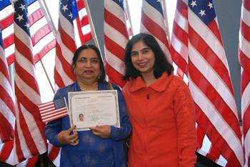 New U.S. citizen Rukmini Punjabi stands proudly with her daughter while displaying her Certificate of Naturalization following the Citizenship Ceremony at the Schaumburg Township District Library. Susan Miura