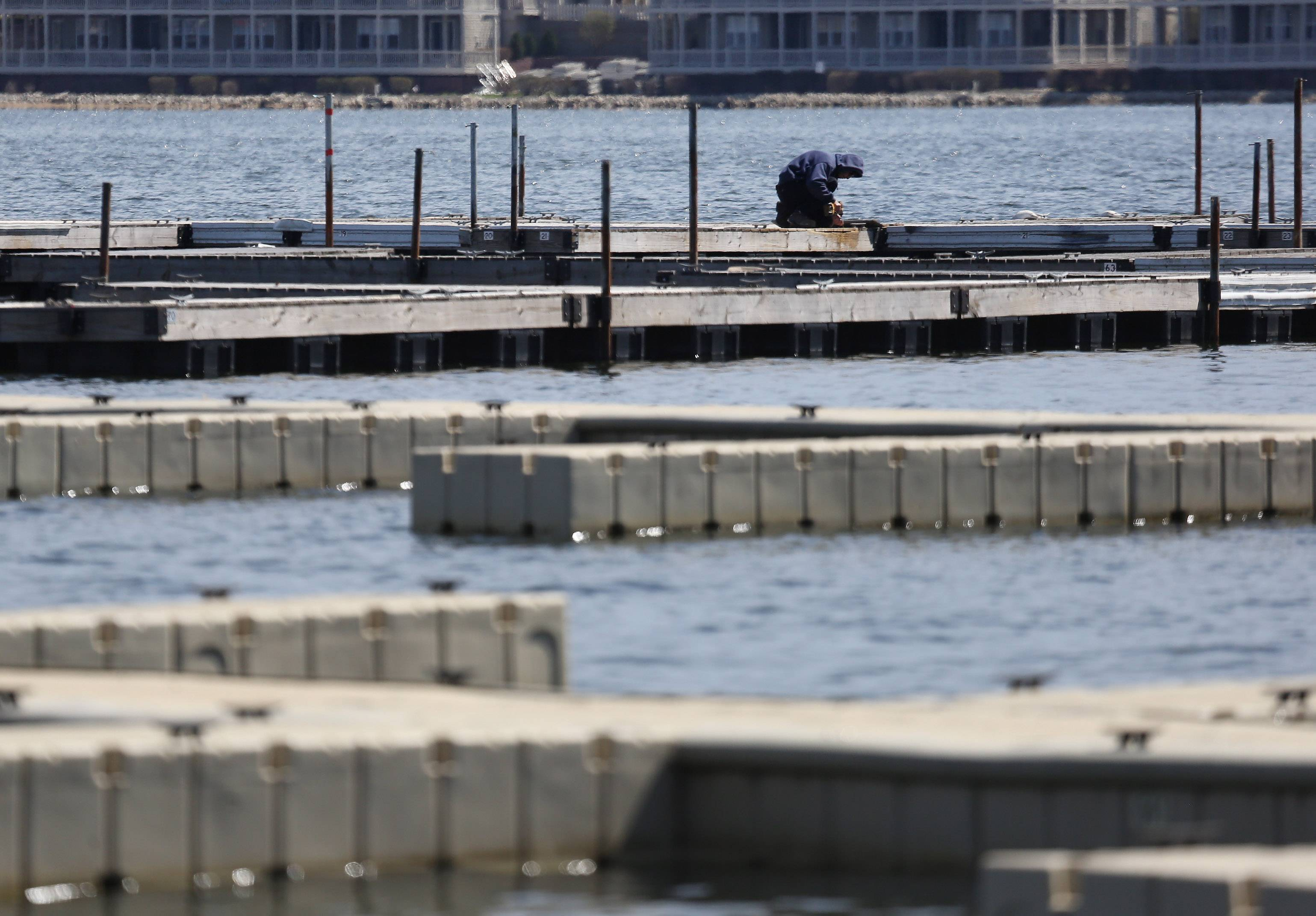 Wauconda Park District employee Alan Emmerich repairs the docks near the beach on Bangs Lake after they were installed this week. The harsh winter caused more damage to the docks than in previous years.