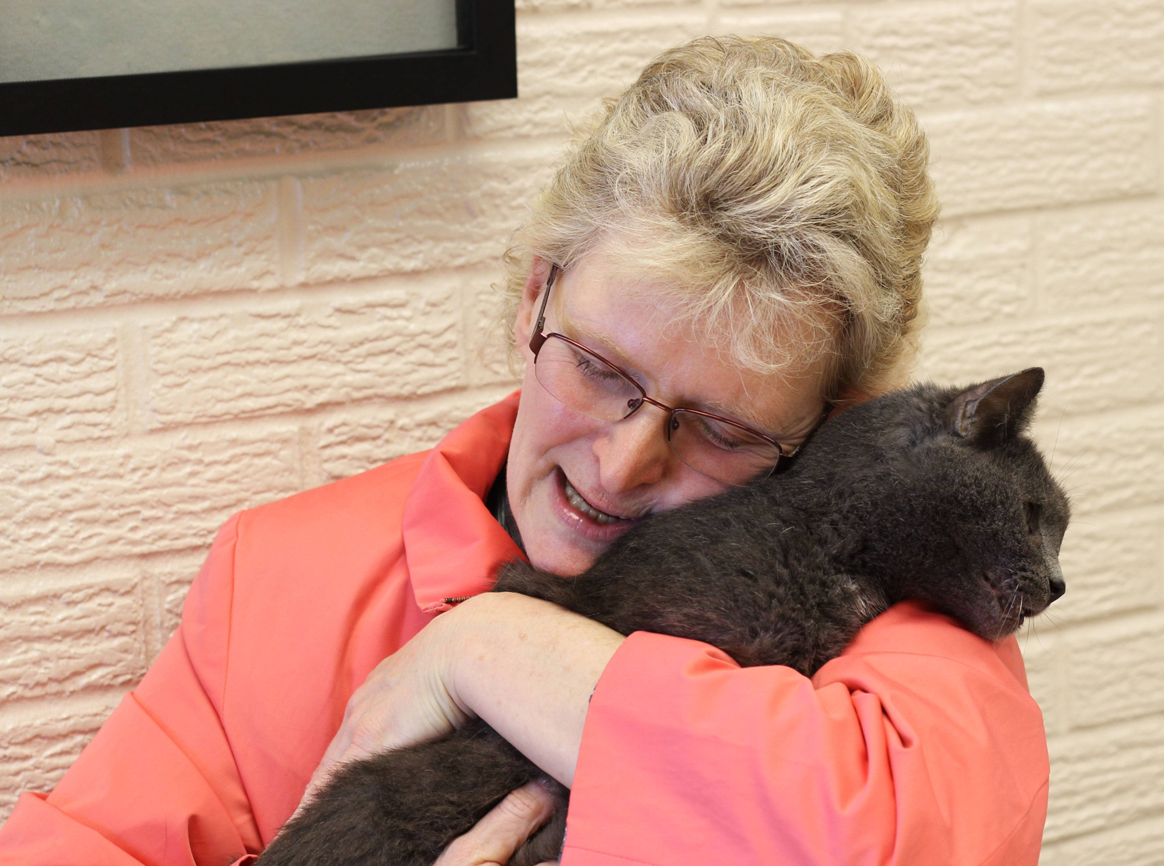 Virginia Fryback hugs her cat, Charlie, at Fort Wayne Animal Care & Control in Fort Wayne, Ind.