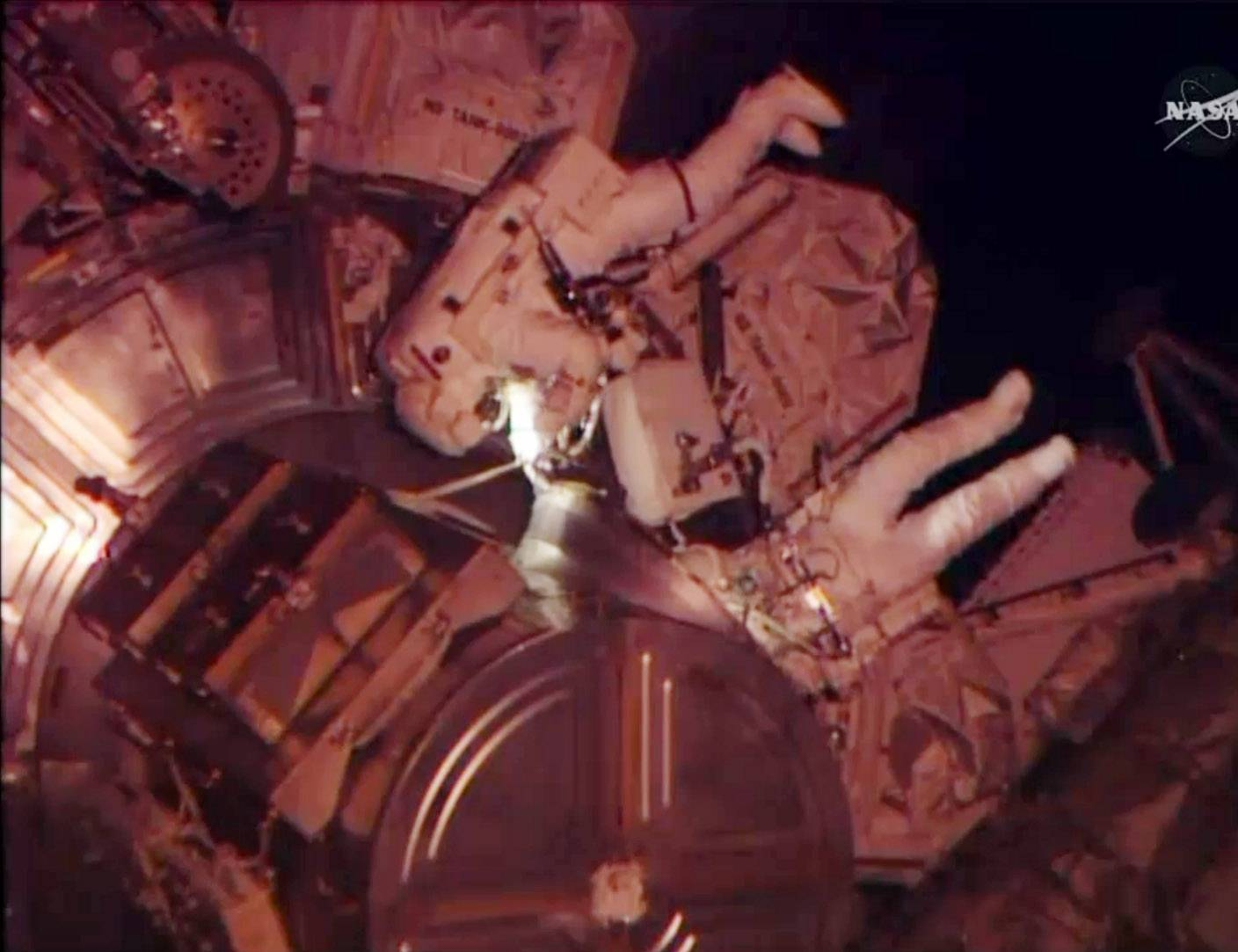 Astronauts Rick Mastracchio and Steven Swanson exit an airlock from the International Space Station. The spacewalk was scheduled to replace a dead computer and get their orbiting home back up to full strength.