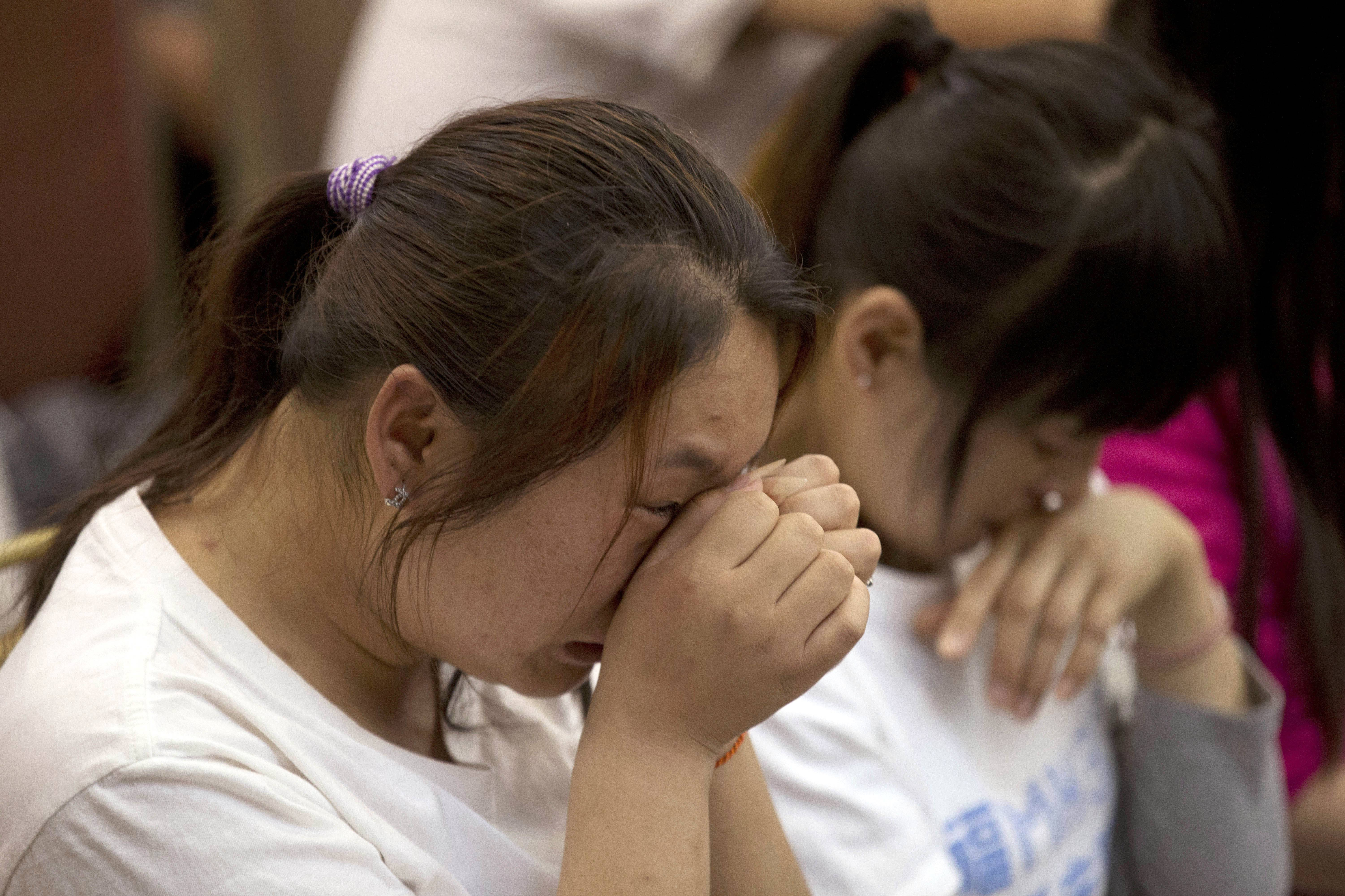Relatives of Chinese passengers onboard the Malaysia Airlines Flight 370, cry during a meeting in Beijing Monday, April 21, 2014.