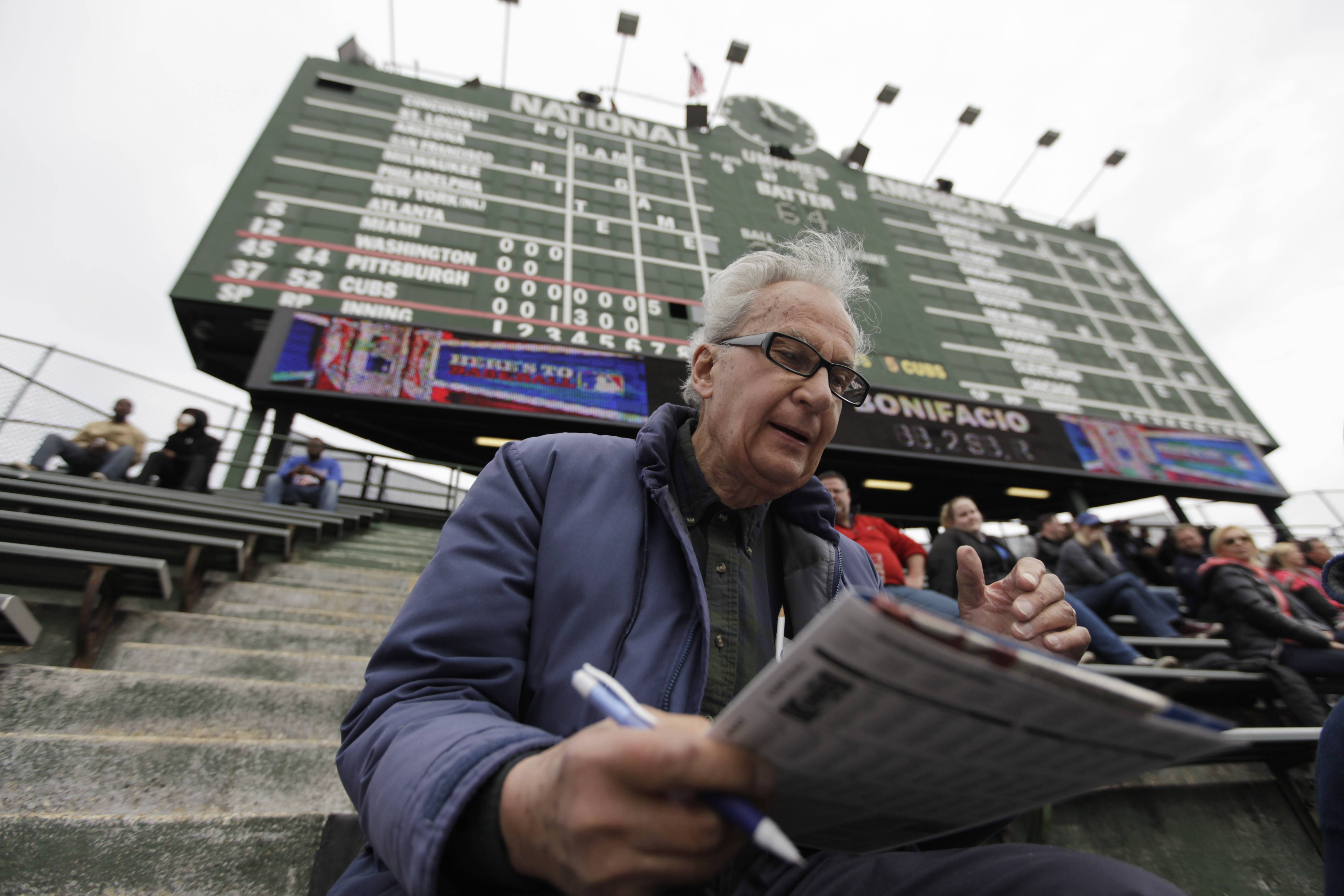 John Weber keeps score with a pencil and scorecard as he watches a baseball game between Pittsburgh Pirates and Chicago Cubs at Wrgley Field.