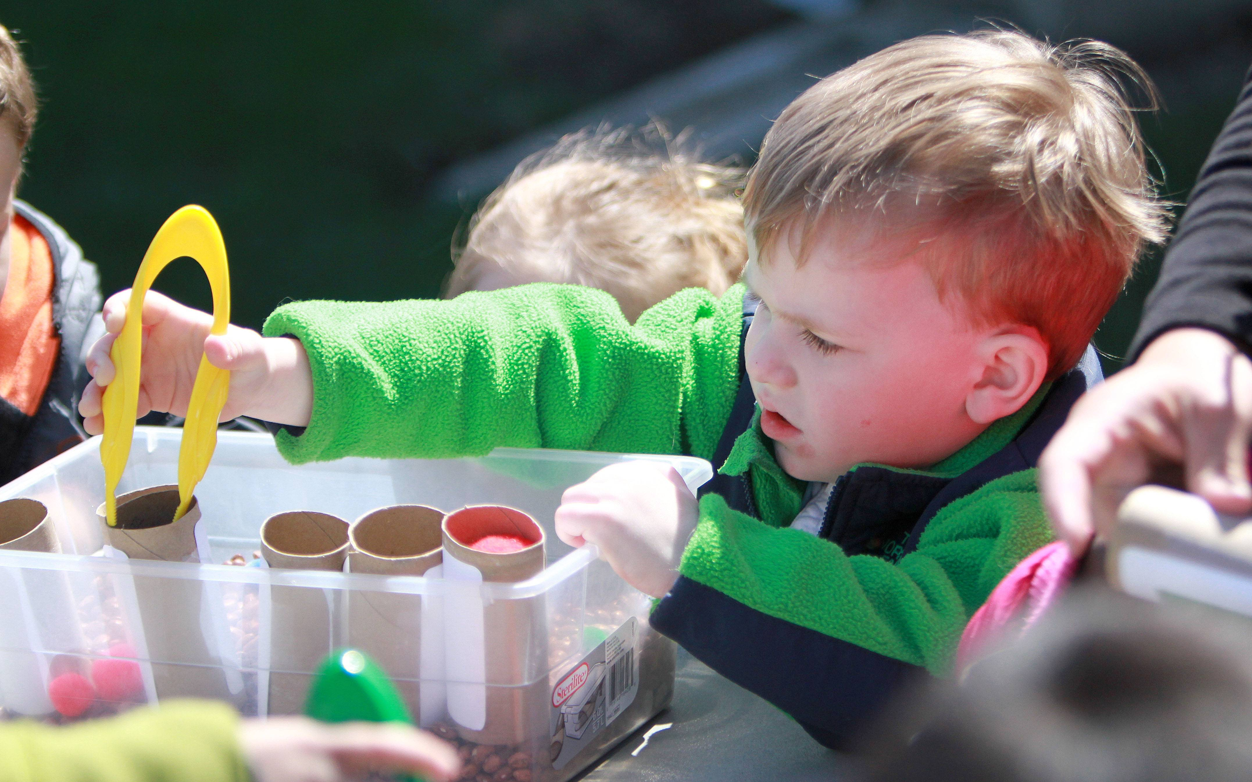 Logan Dietz, 3, participates in a color sorting activity as Woodland Primary students celebrate Earth Day on Tuesday in Gages Lake.