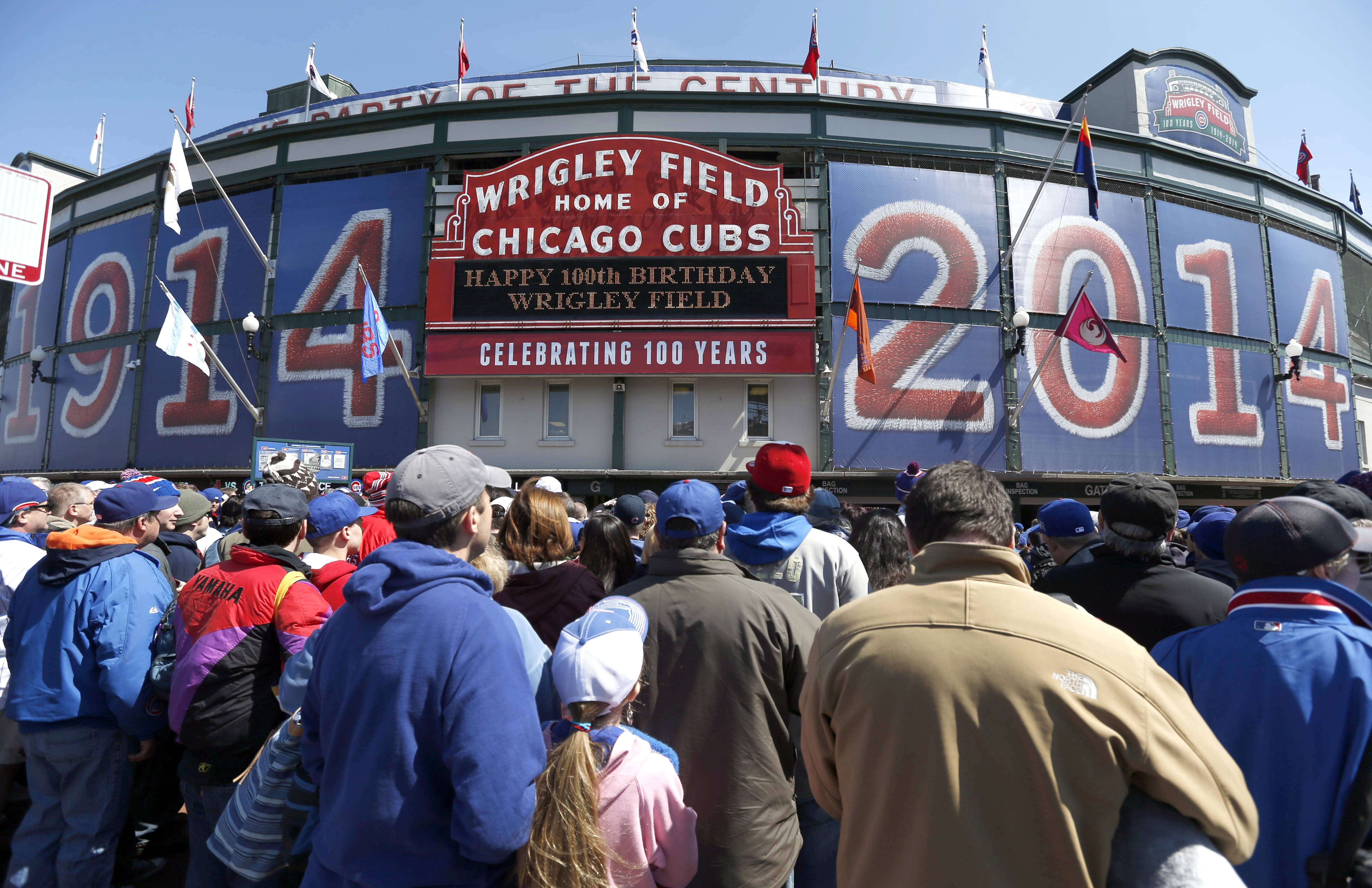 Baseball fans wait to enter Wrigley Field Wednesday on the 100th anniversary of the first baseball game at the park.