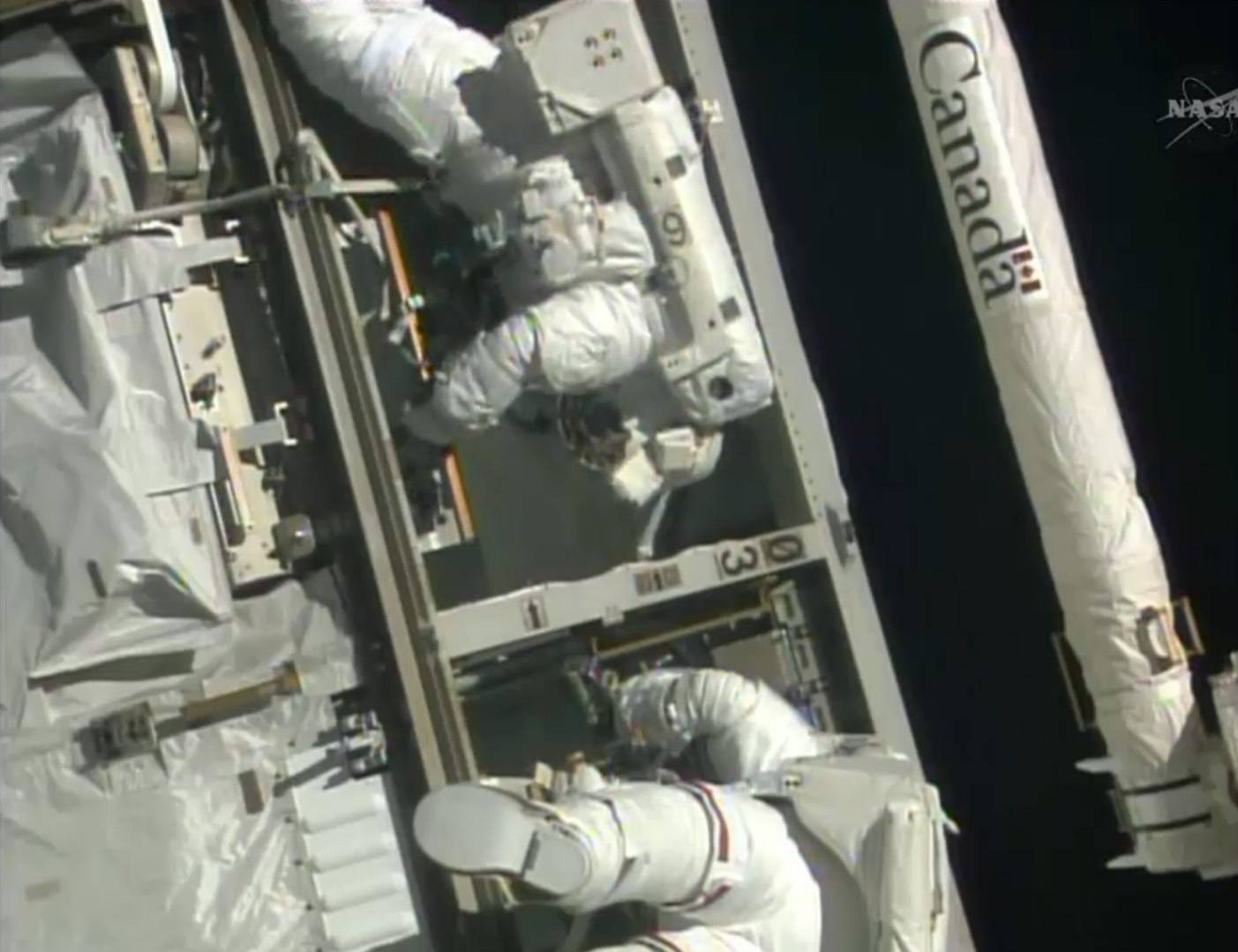 Astronauts Steven Swanson, left, and Rick Mastracchio perform a spacewalk outside the International Space Station to replace a dead computer. The device is a critical backup outside the station that failed nearly two weeks ago. The prime computer has been working fine, but NASA wanted to install a fresh spare as soon as possible.
