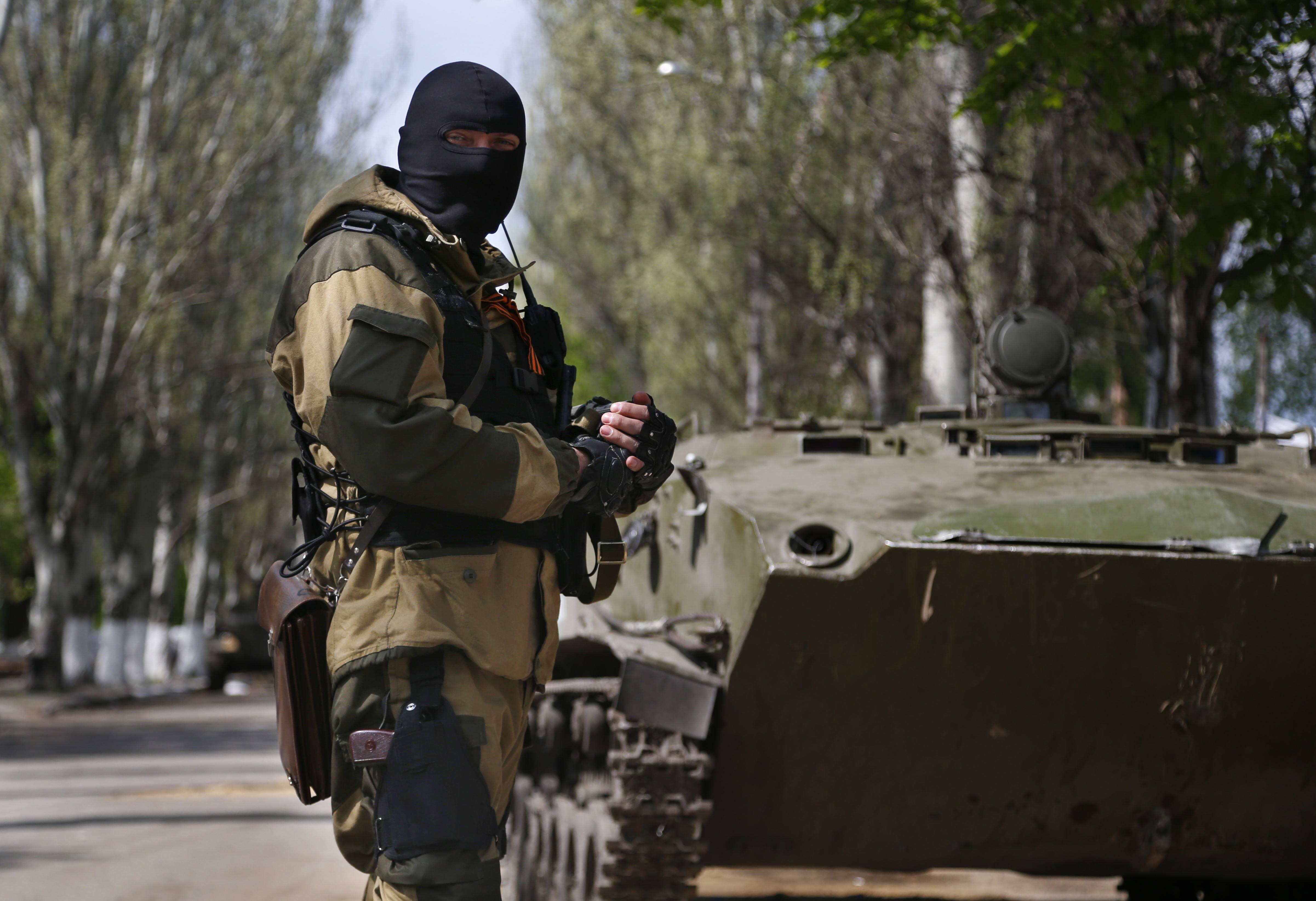 "A pro-Russian masked gunman patrols a street in the center of Slovyansk, eastern Ukraine, Wednesday. Pro-Russian gunmen in eastern Ukraine admitted on Wednesday that they are holding an American journalist, saying he was suspected of unspecified ""bad activities."""