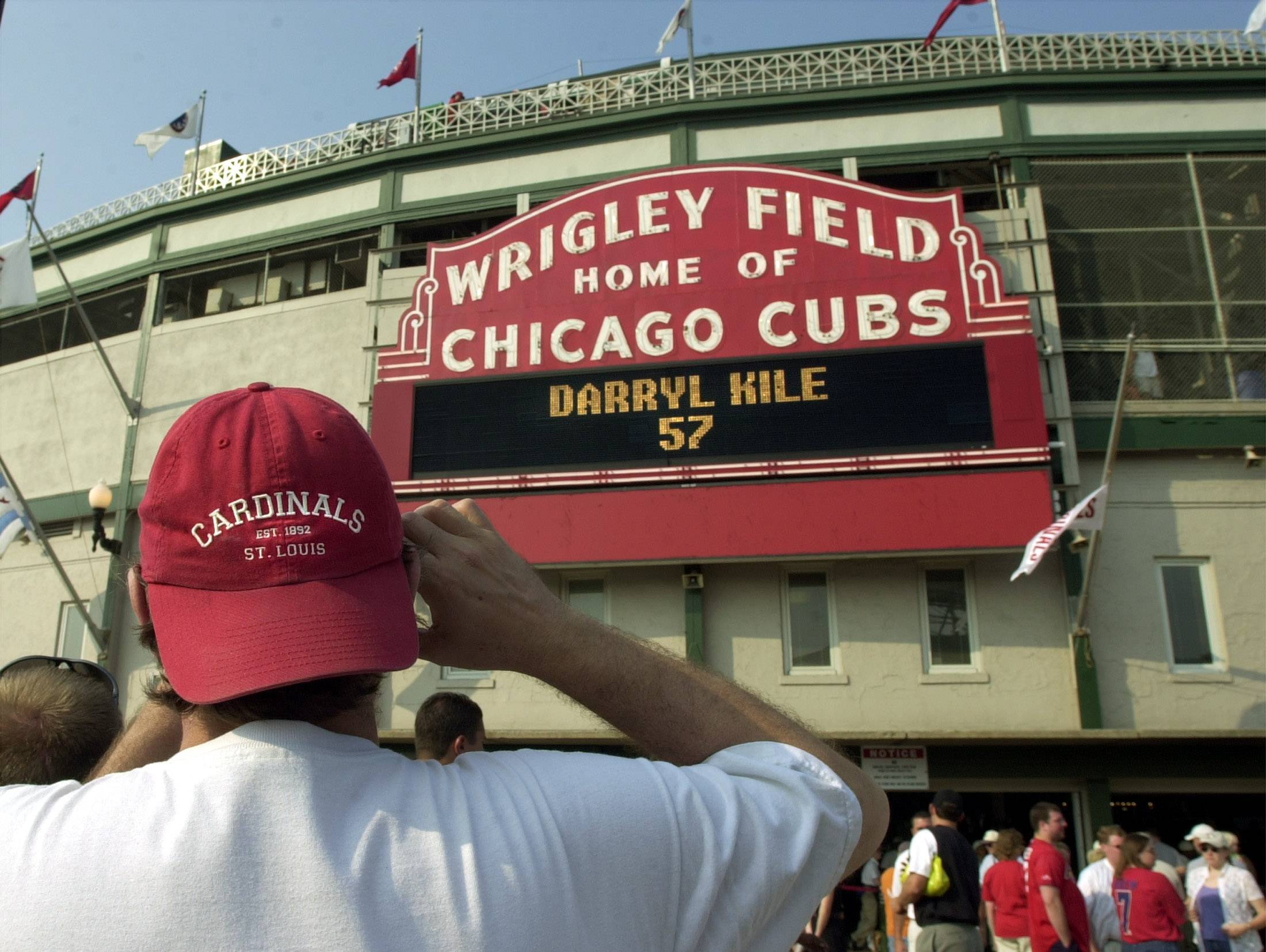 A St. Louis Cardinals fan takes a picture of the Wrigley Field marquee before a game against the Chicago Cubs.