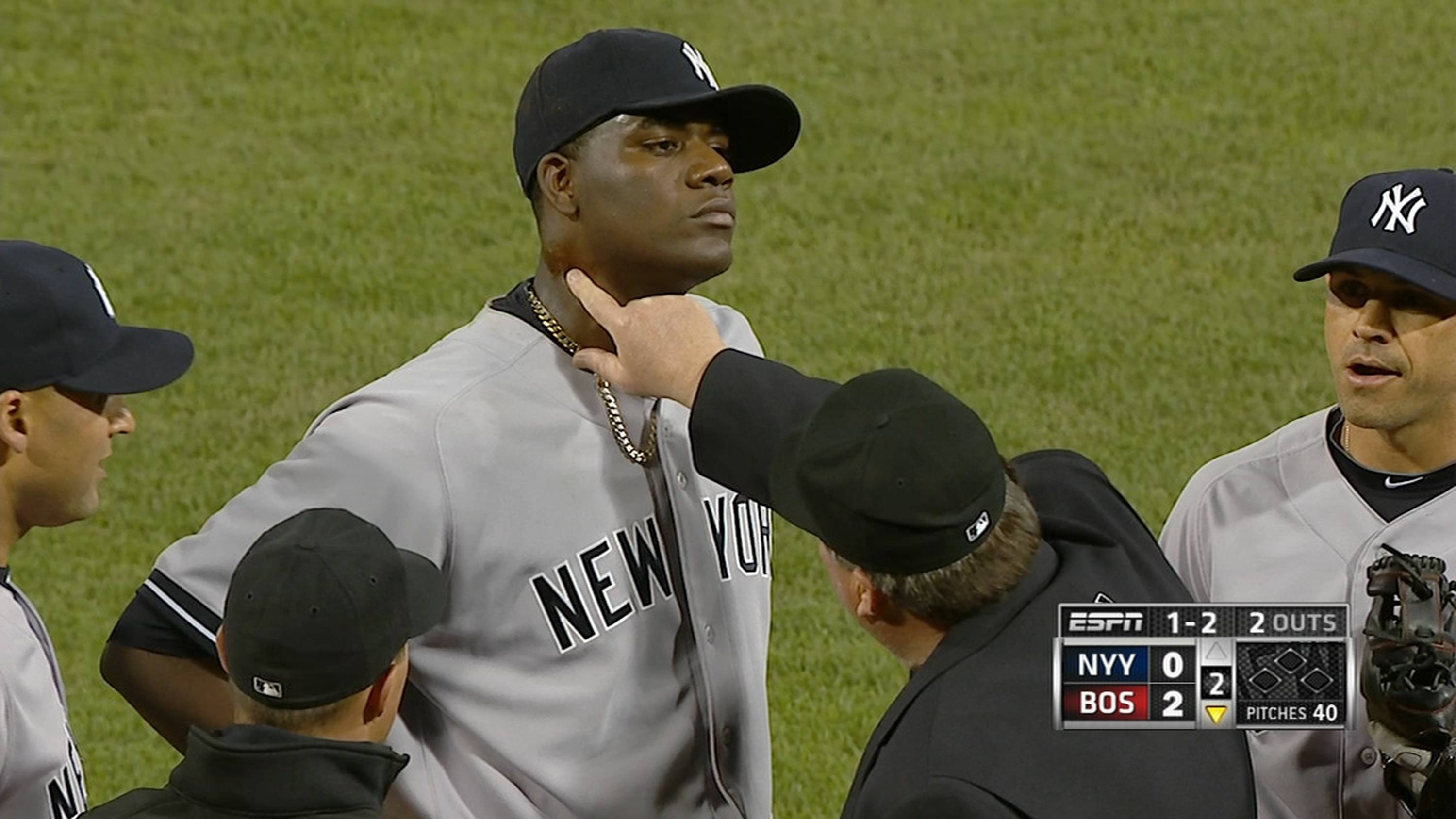 In this April 23, 2014 photo taken from video and provided by ESPN, home plate umpire Gerry Davis touches the neck of New York Yankees starting pitcher Michael Pineda in the second inning of the Yankees' baseball game against the Boston Red Sox at Fenway Park in Boston. Pineda was ejected after umpires found a foreign substance on his neck.
