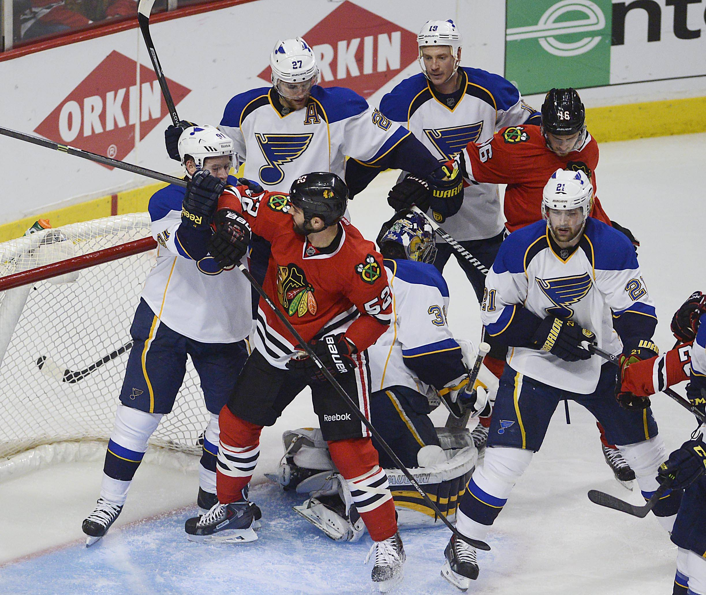 Chicago Blackhawks and St. Louis Blues players tangle in front of the Chicago net .