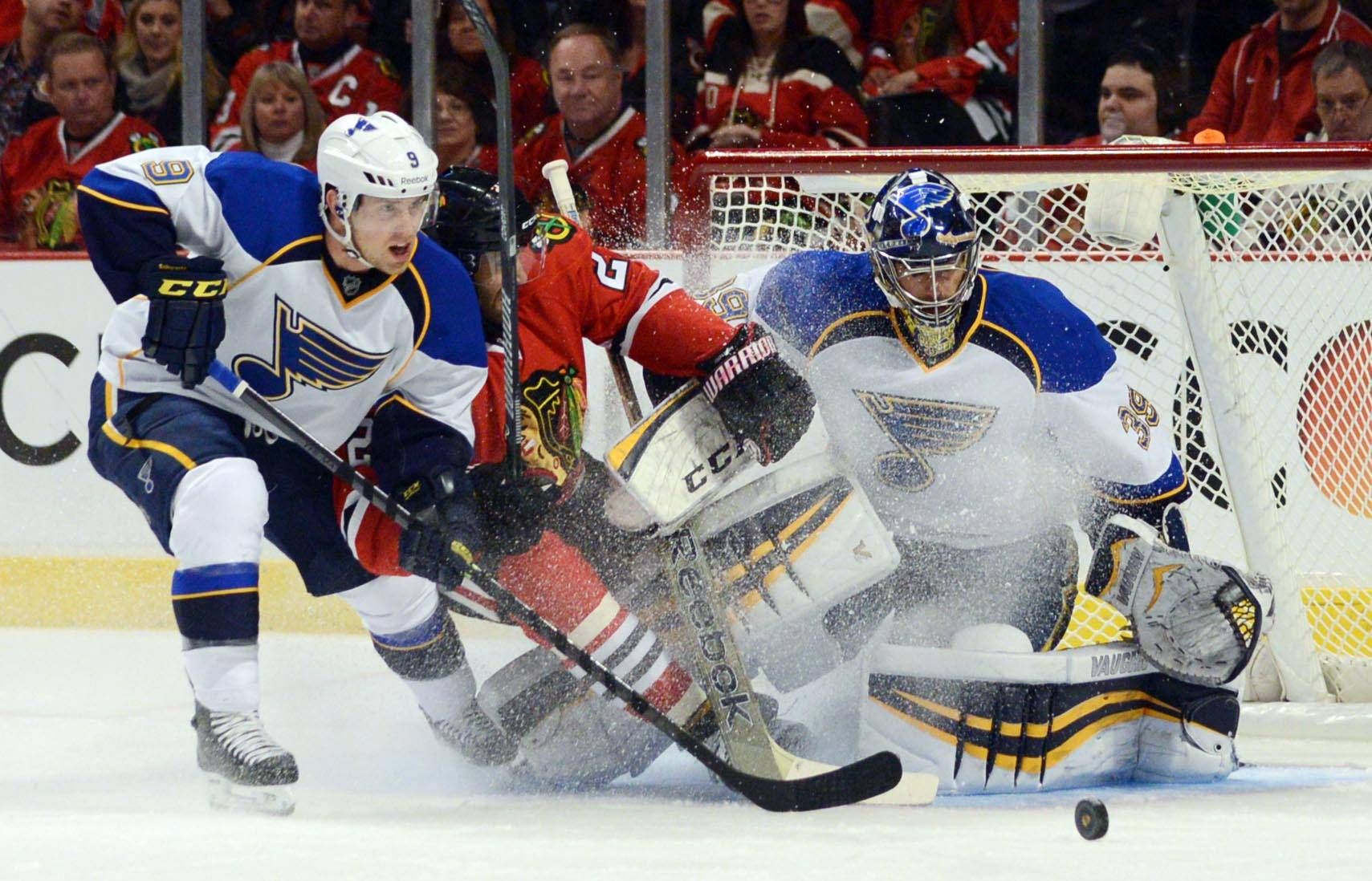 Chicago Blackhawks defenseman Johnny Oduya is blocked from the puck by St. Louis Blues left wing Jaden Schwartz in front of the net.
