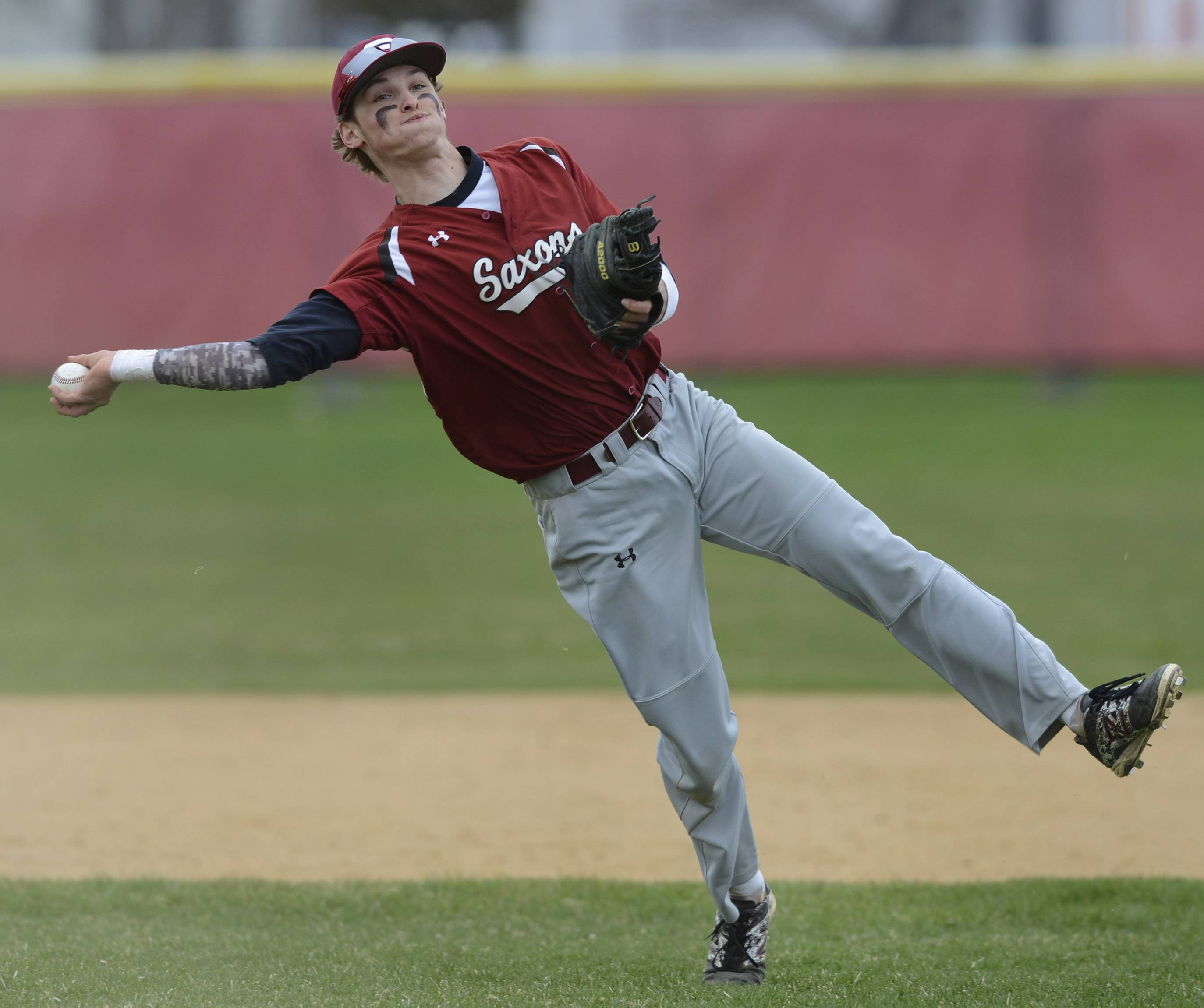 Schaumburg's Joe Franz hustles to make a throw after picking up a slow roller, just missing the Conant runner at first.