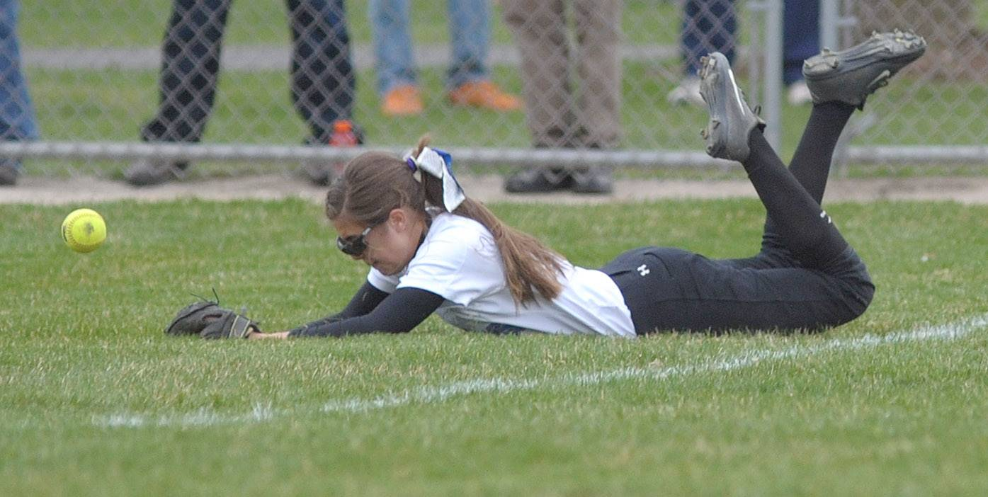 Geneva's Sarah Baurer dives for a ball just past the foul line in the fifth inning on Wednesday, April 23.